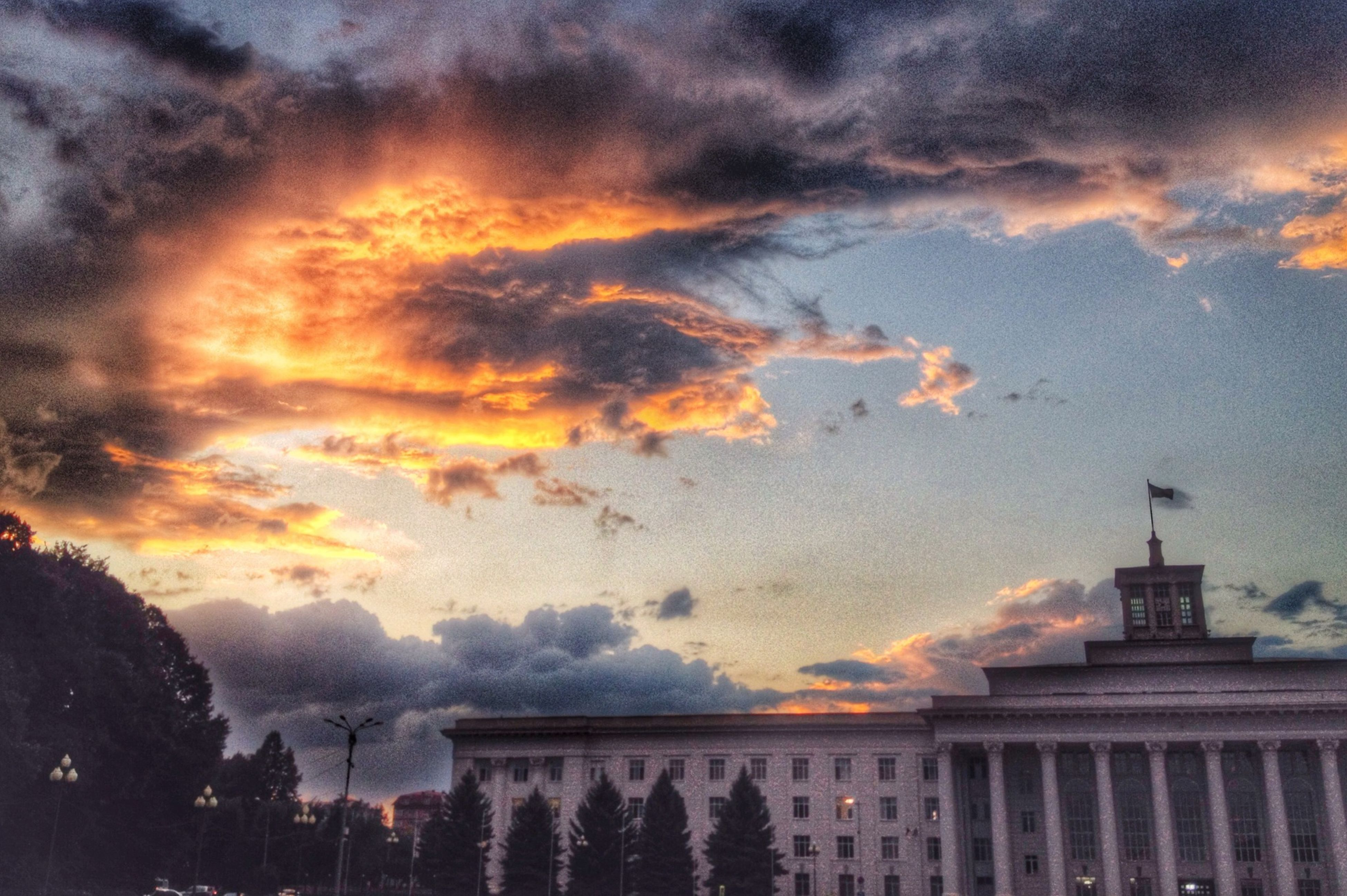 cloud - sky, sunset, sky, cloudy, weather, dramatic sky, architecture, orange color, built structure, building exterior, overcast, storm cloud, scenics, beauty in nature, atmospheric mood, nature, silhouette, cloud, idyllic, moody sky