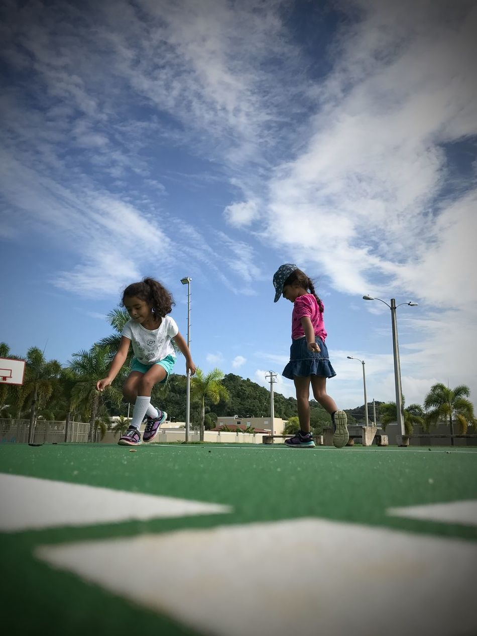 Togetherness Low Angle View Childhood Outdoors Girls Children Only Day Sky Real People Full Length Playing Kids Playing Youth Sisters Playing Together Playing Outside People In Motion Family Point Of View Millennial Pink Break The Mold
