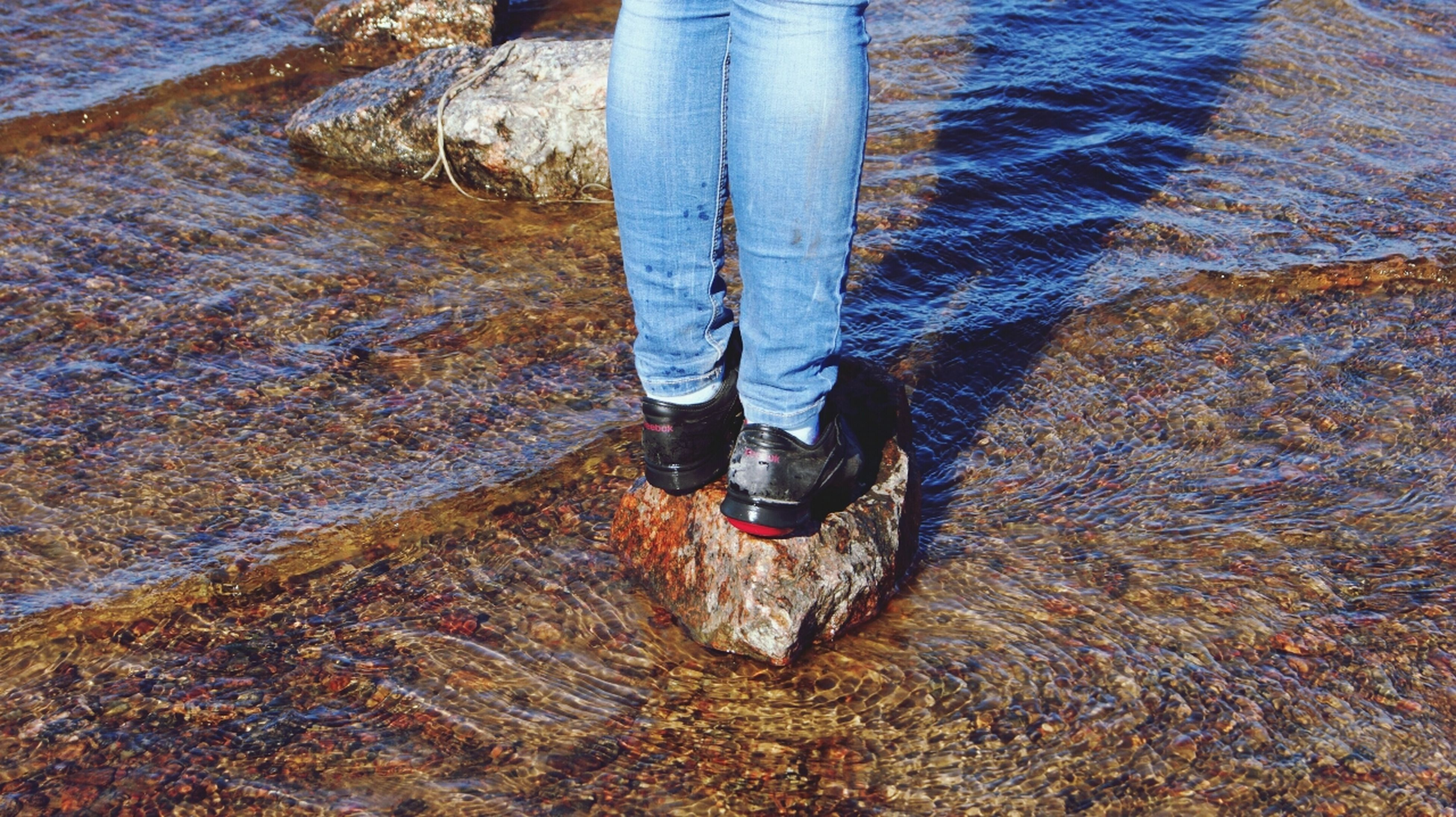 low section, person, lifestyles, shoe, standing, leisure activity, human foot, men, water, high angle view, jeans, footwear, outdoors, casual clothing, day, unrecognizable person