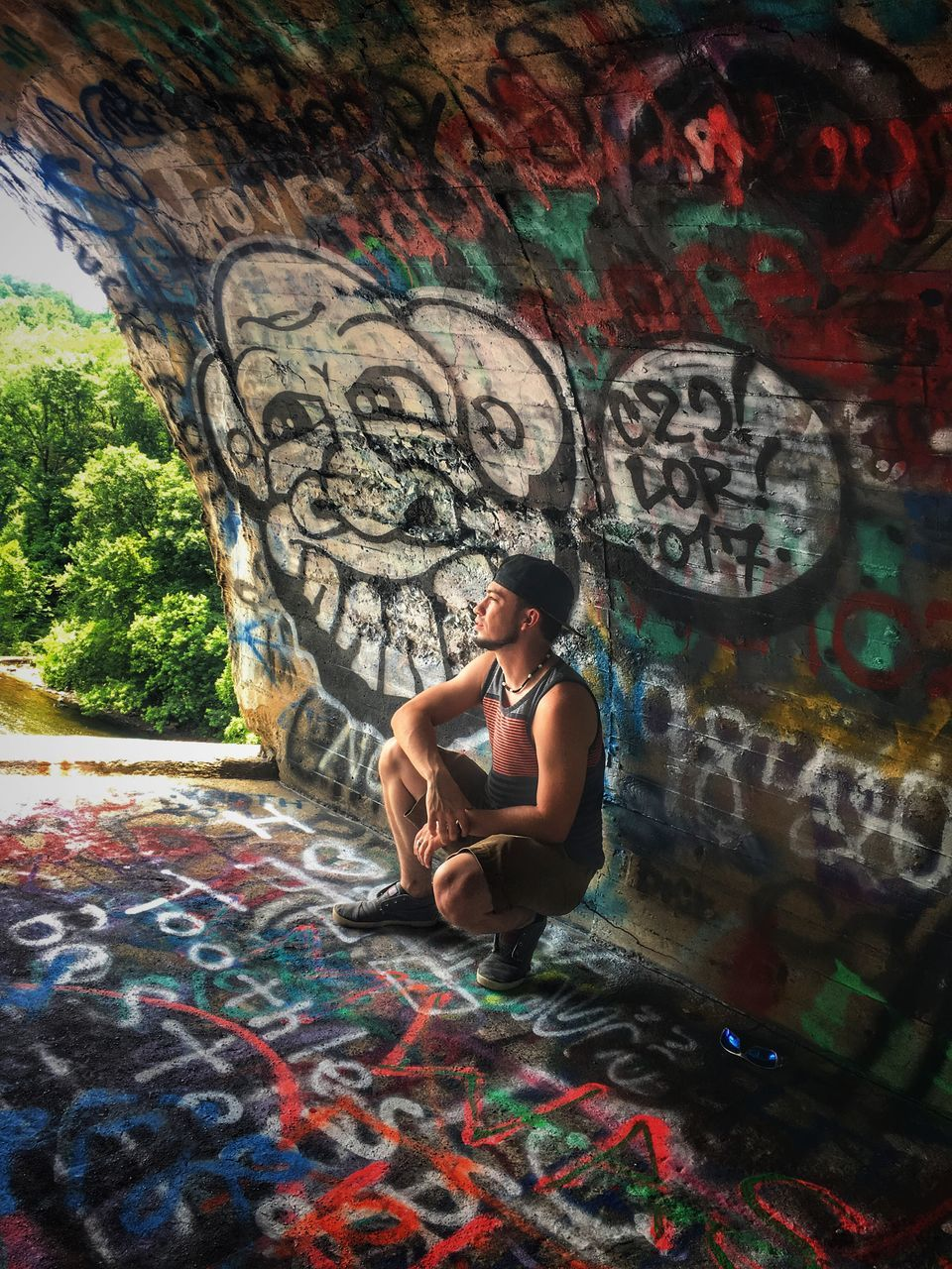 graffiti, art and craft, real people, one person, lifestyles, street art, full length, leisure activity, young adult, multi colored, artist, day, outdoors, sitting, young women, architecture, tree, people
