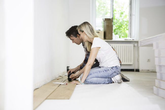 Young couple laying a laminate floor in yoga studio. Casual Clothing Couple Day Domestic Room Floor Full Length Laminate Laying A Floor Leaning Leisure Activity Lifestyles Measuring Renovations Sensuality Teamwork