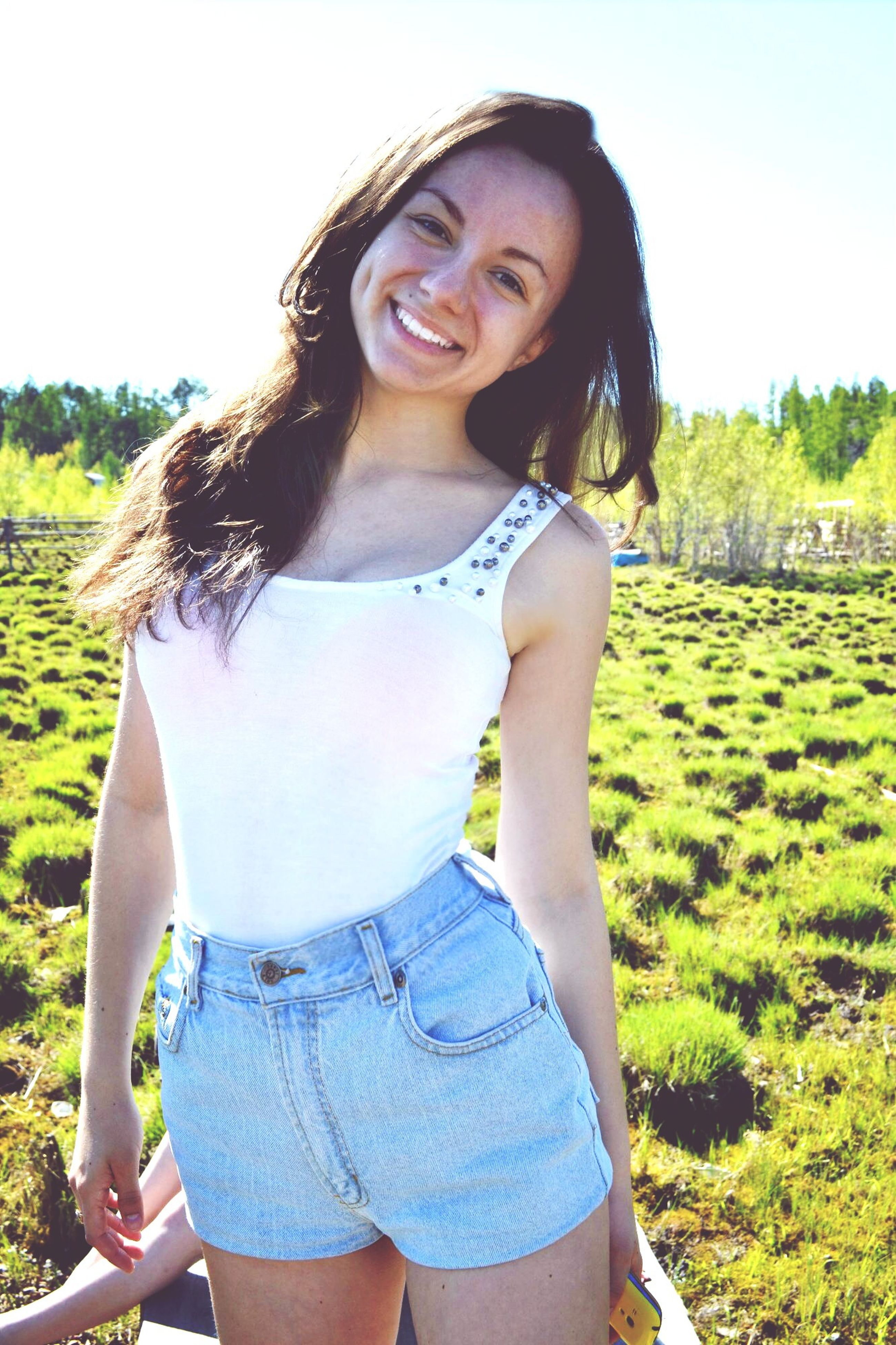 young adult, person, looking at camera, portrait, young women, casual clothing, lifestyles, front view, smiling, standing, leisure activity, three quarter length, happiness, long hair, sunglasses, toothy smile, outdoors