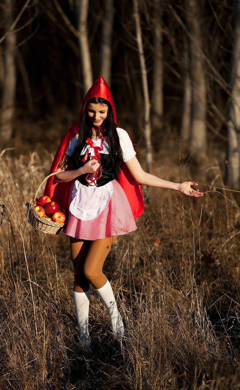 lifestyles, real people, front view, one person, leisure activity, full length, field, fashion, red, outdoors, portrait, looking at camera, young women, happiness, girls, standing, smiling, childhood, young adult, day, halloween, witch