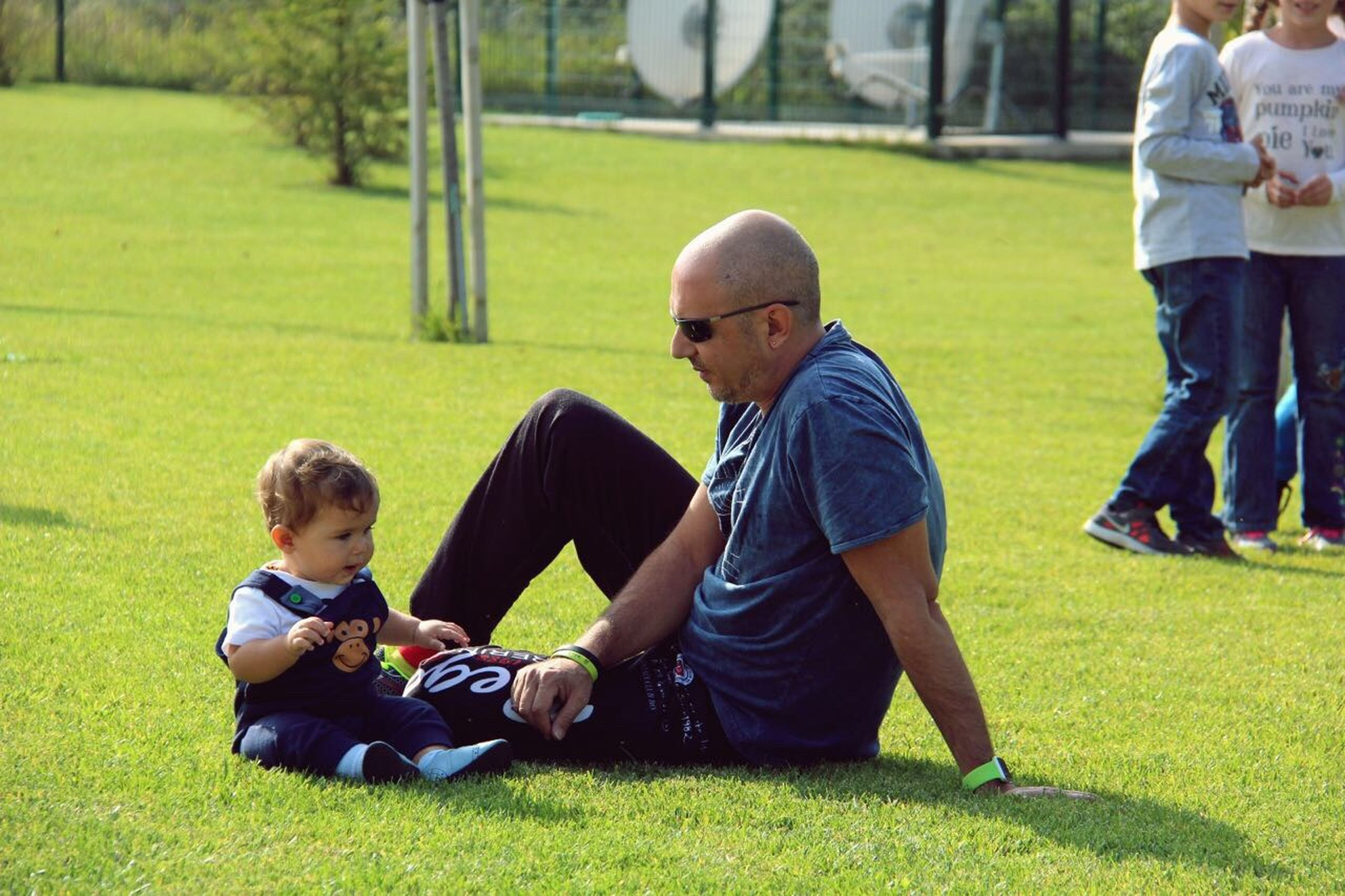 child, leisure activity, sitting, people, sport, outdoors, grass, soccer, bonding, day, togetherness, adult, childhood, playing, soccer field, sportsman, ball, athlete, young adult, track and field stadium, golfer