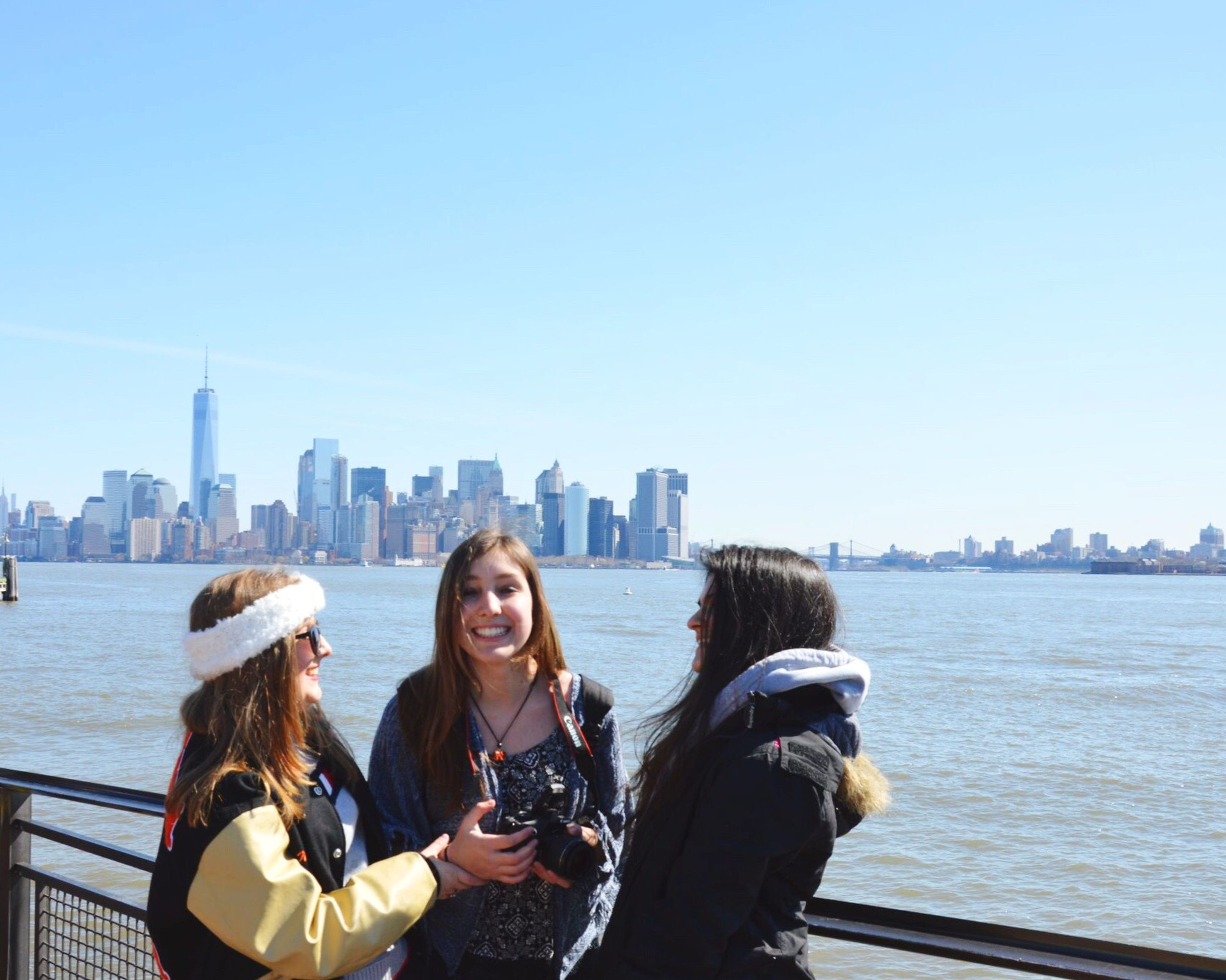 lifestyles, city, clear sky, leisure activity, water, cityscape, copy space, architecture, young adult, building exterior, built structure, sitting, sea, skyscraper, urban skyline, waist up, person, young women