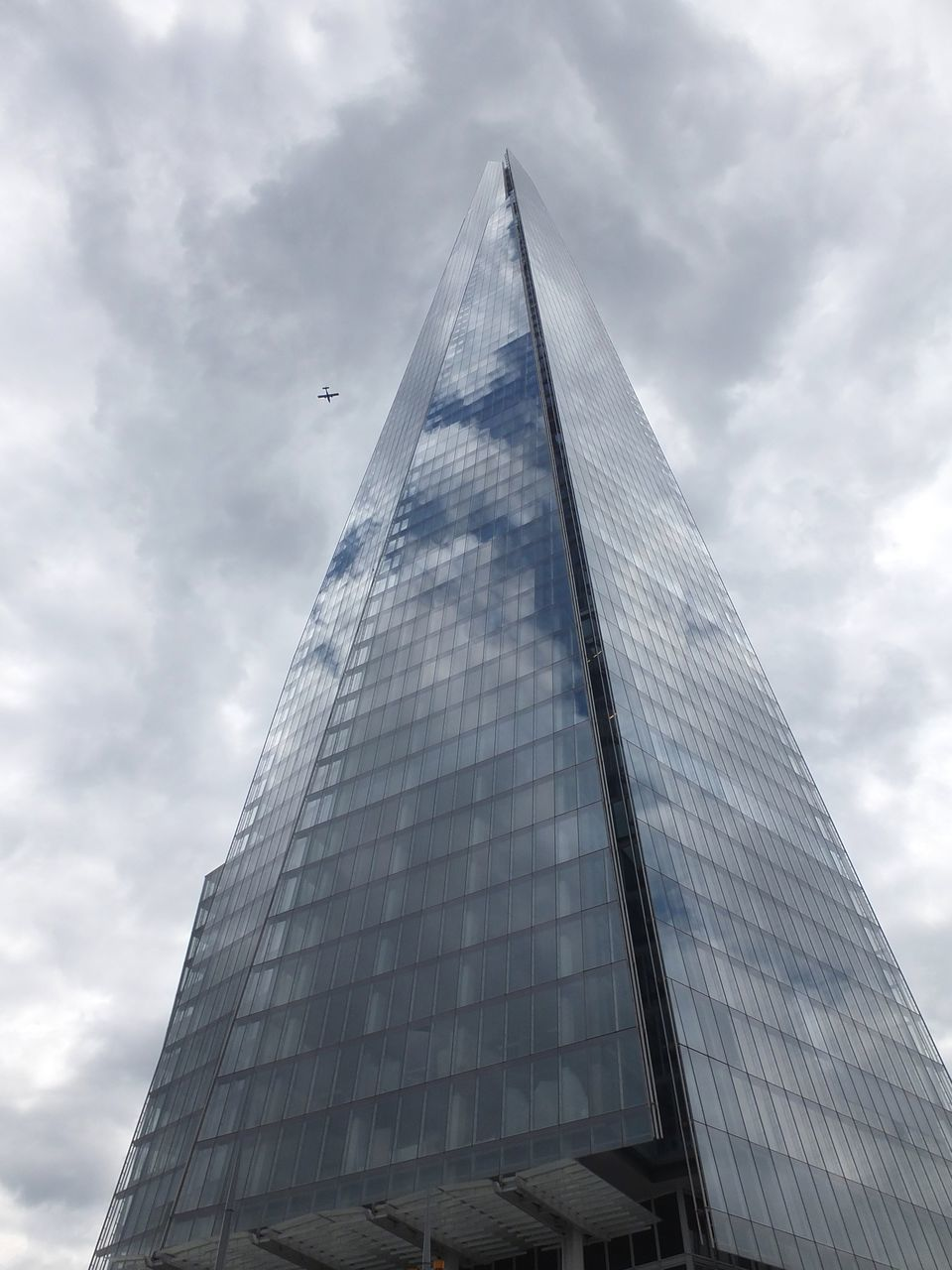architecture, built structure, tower, skyscraper, tall - high, modern, building exterior, low angle view, sky, pyramid, cloud - sky, day, city, no people, tall, travel destinations, outdoors