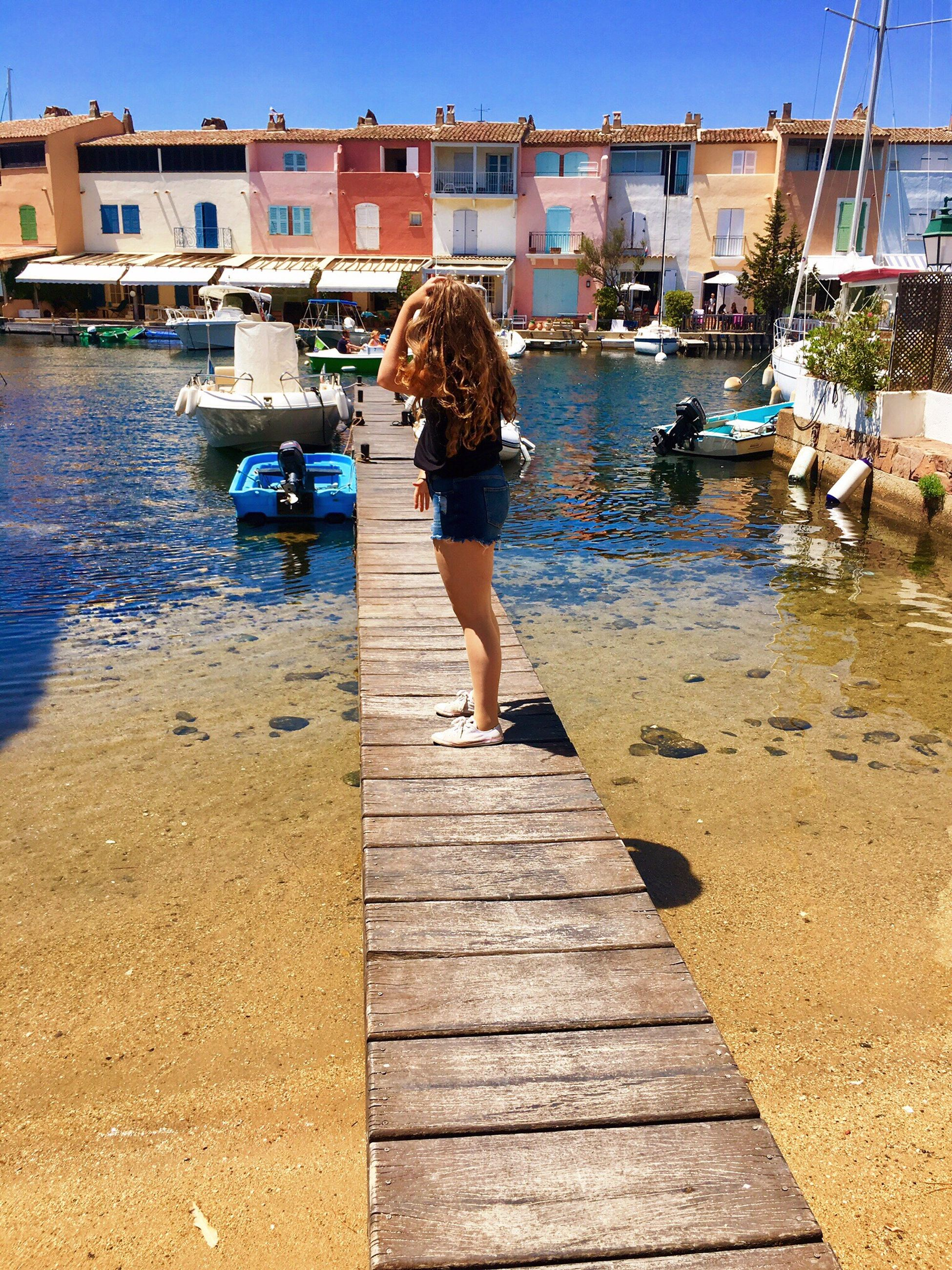 water, real people, built structure, rear view, architecture, one person, building exterior, day, outdoors, full length, women, lifestyles, nature, clear sky, young adult, young women, sky, people