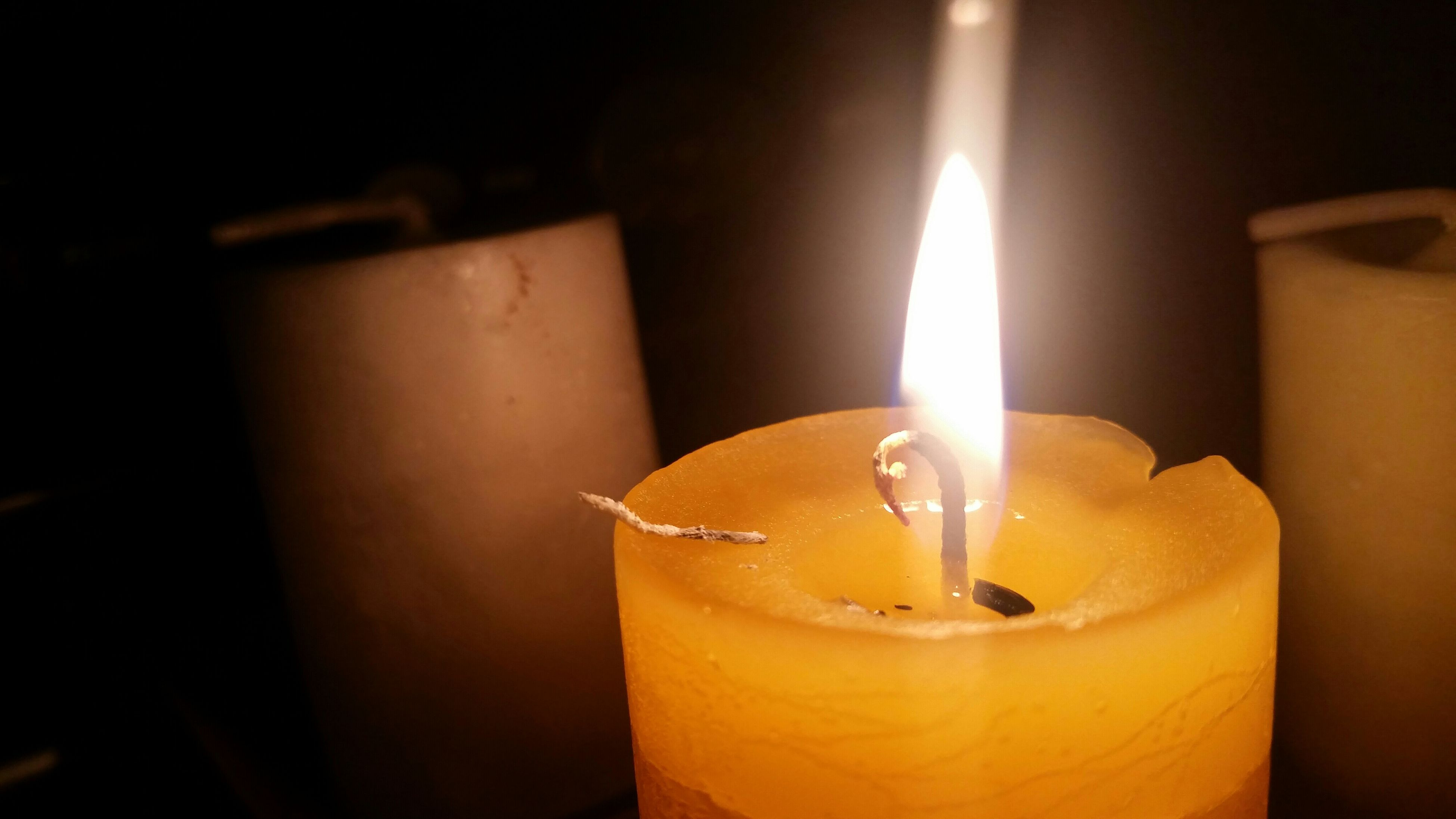 burning, flame, candle, glowing, indoors, illuminated, close-up, heat - temperature, fire - natural phenomenon, lit, candlelight, light - natural phenomenon, lighting equipment, still life, no people, focus on foreground, glass - material, dark, wall - building feature, yellow