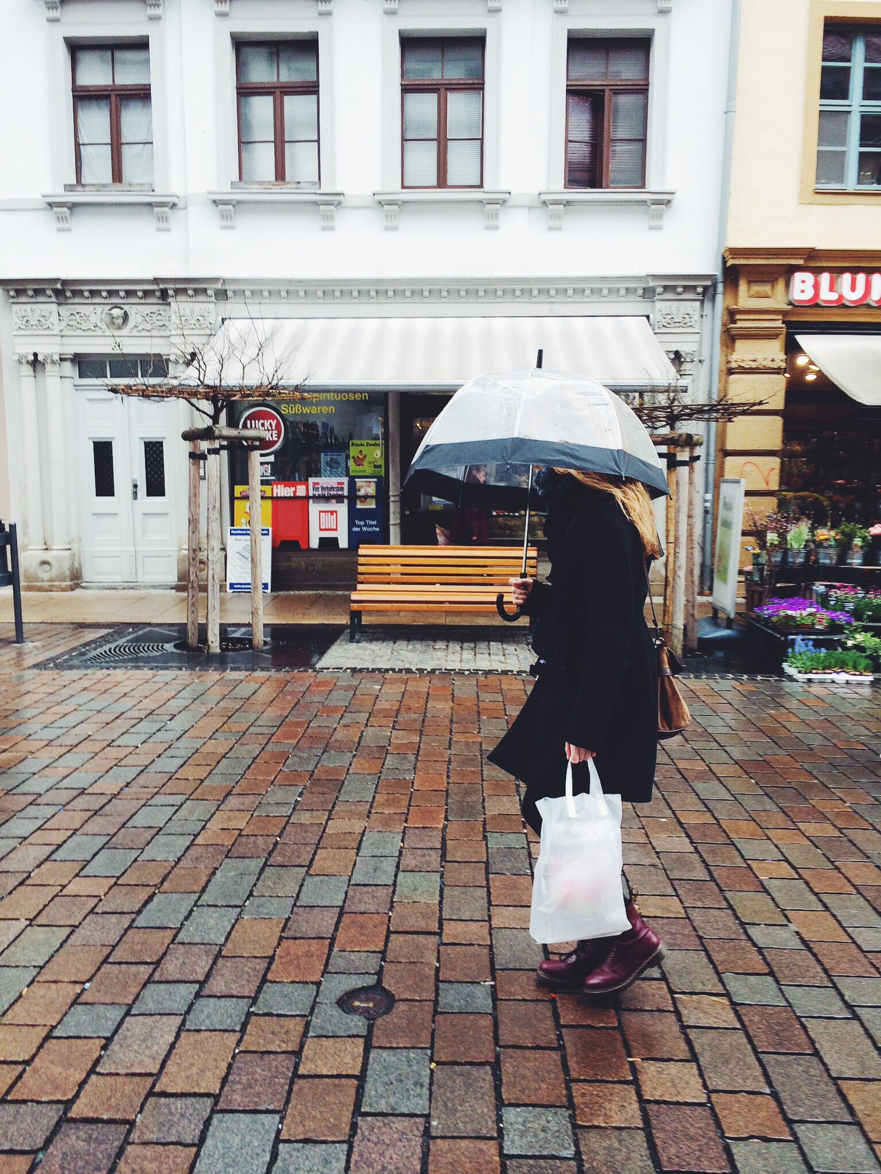 Side View Of Woman Holding Umbrella While Walking On Wet Sidewalk