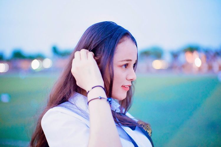 Young Adult Headshot Young Women Focus On Foreground One Person Real People Leisure Activity Listening Using Phone One Young Woman Only Wireless Technology Headphones Lifestyles Day Women Technology One Woman Only Sky Only Women
