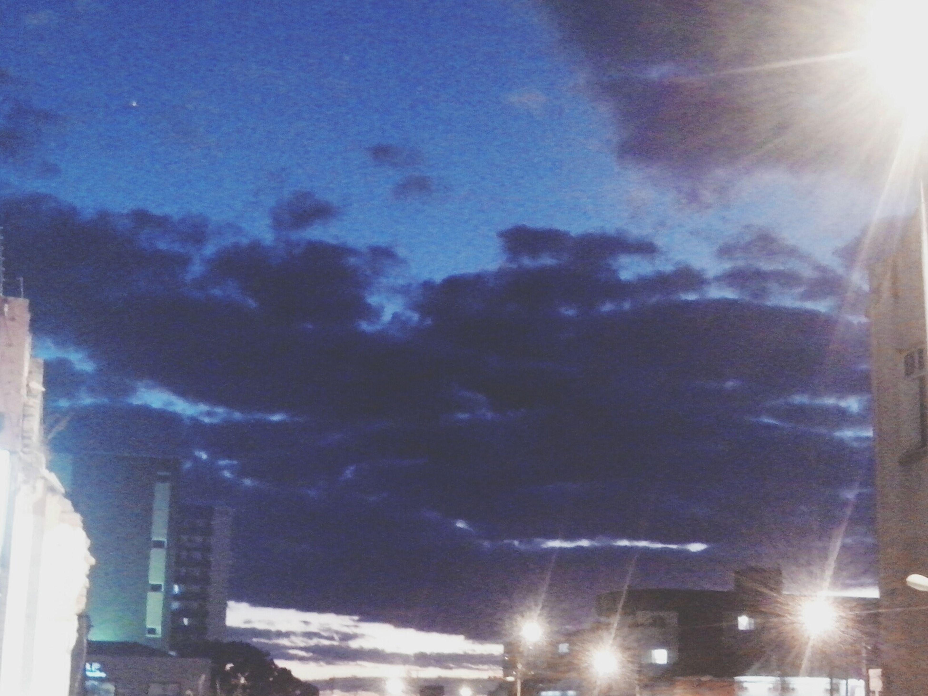 low angle view, sky, built structure, sunbeam, lens flare, building exterior, sun, architecture, street light, sunlight, illuminated, city, night, cloud - sky, car, silhouette, outdoors, building, transportation, no people