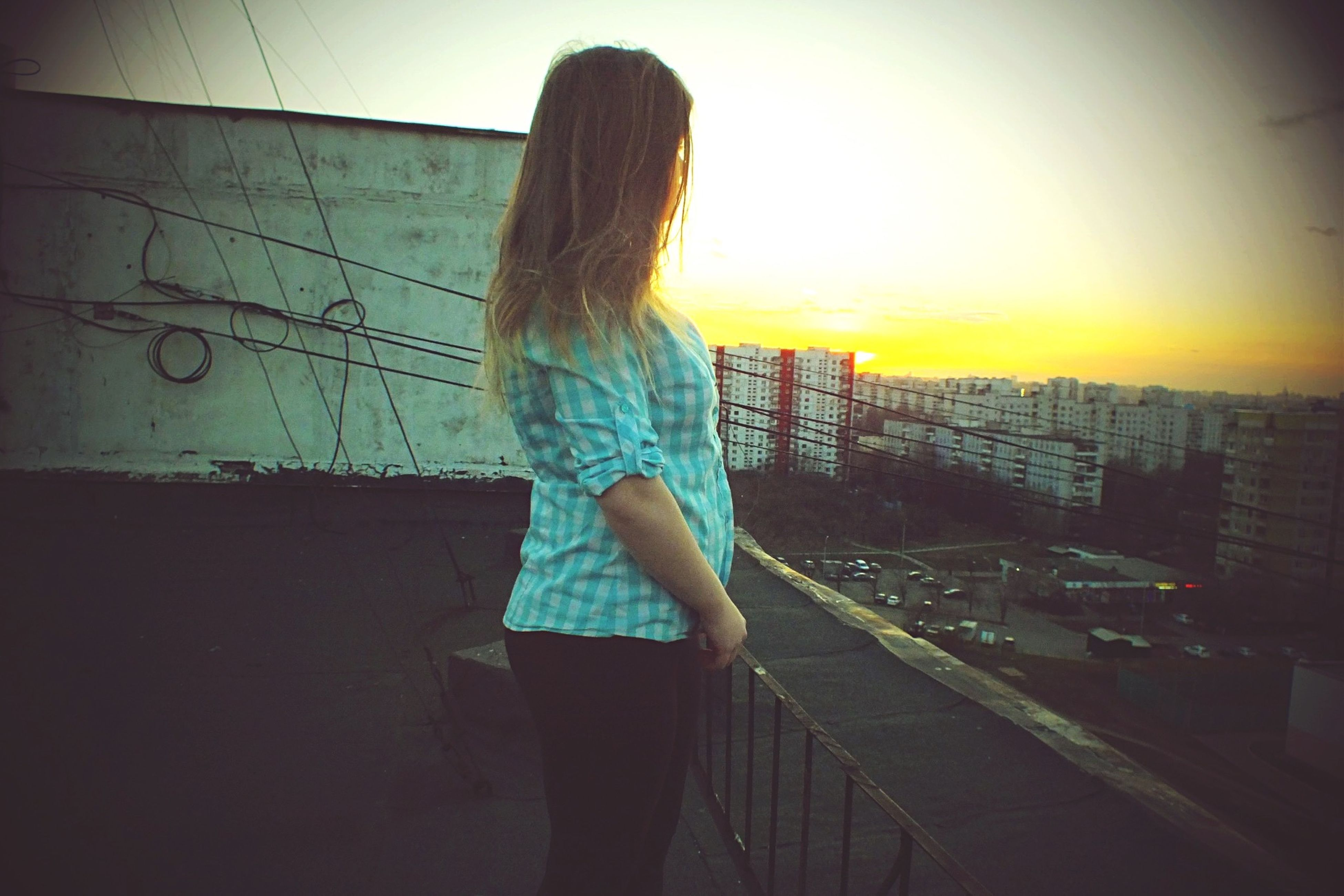 lifestyles, standing, leisure activity, casual clothing, full length, rear view, young women, built structure, architecture, young adult, person, building exterior, three quarter length, long hair, sunlight, city, side view, sunset
