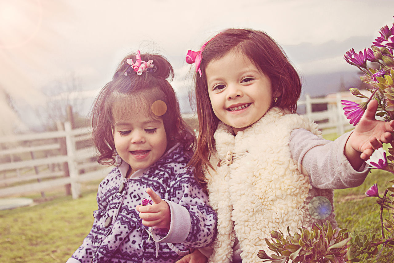 Baby Beauty In Nature Cheerful Child Childhood Cute Daughter Family Females Flower Fun Girls Happiness Innocence Joy Looking At Camera Love Mother Nature Outdoors People Portrait Smiling Togetherness
