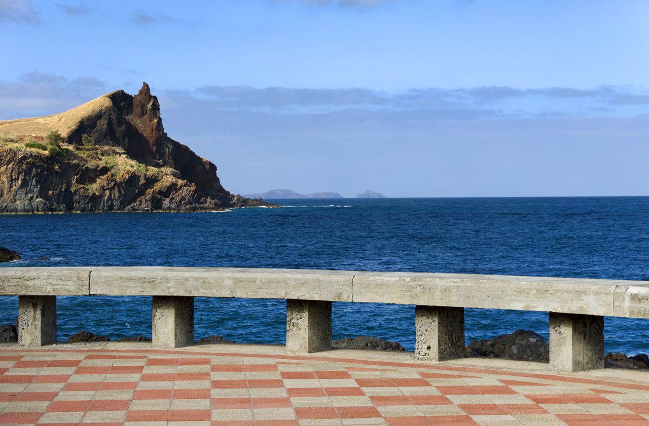 Scenic View Of Mountain By Sea Against Sky Seen From Promenade