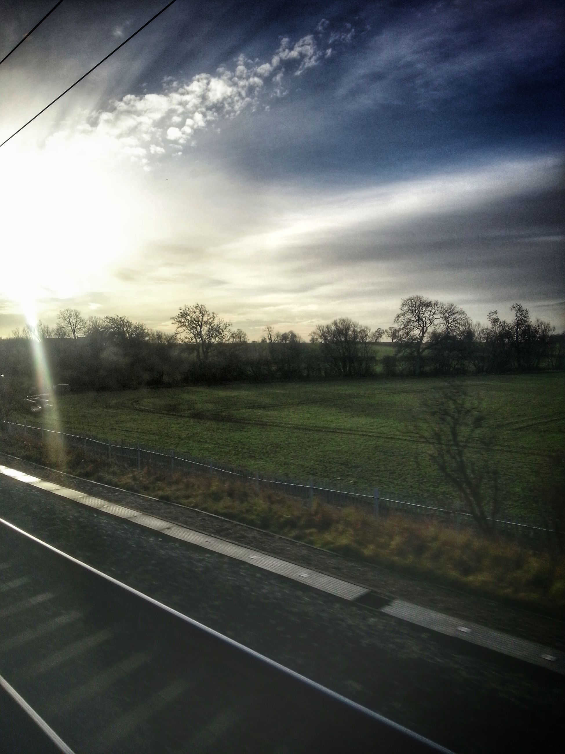 transportation, road, tree, sky, cloud - sky, landscape, sunlight, road marking, the way forward, country road, field, cloud, nature, railroad track, sun, sunbeam, growth, no people, street, day