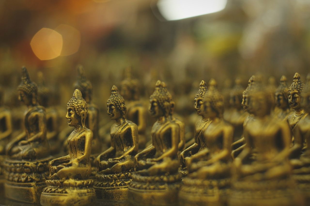 Close-Up Of Golden Buddha Statues Arranged In Temple