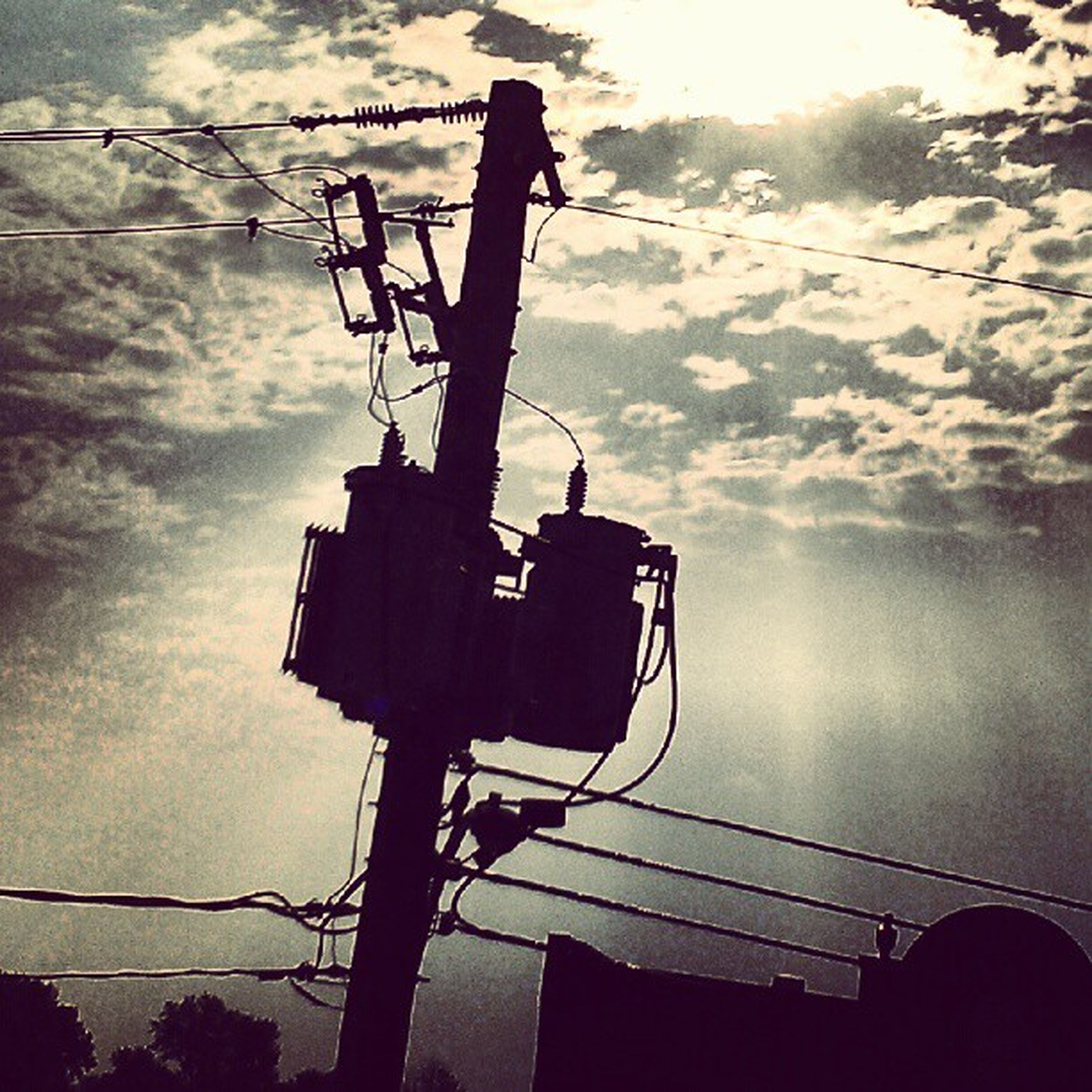 power line, low angle view, electricity pylon, electricity, sky, silhouette, power supply, cable, fuel and power generation, technology, connection, cloud - sky, cloudy, dusk, built structure, weather, power cable, architecture, crane - construction machinery, outdoors