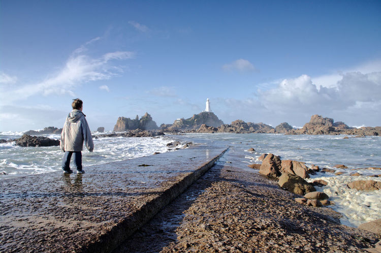 a young man walks towards the causeway and then stops and stares at the sight of the lighthouse and the crashing waves Alone Blue Sky Causeway Forbidding Grand Imposing In Awe La Corbiere Landscape Large Coat Lighthouse Standing Sunny Day Watching Young Man Telling Stories Differently Movement