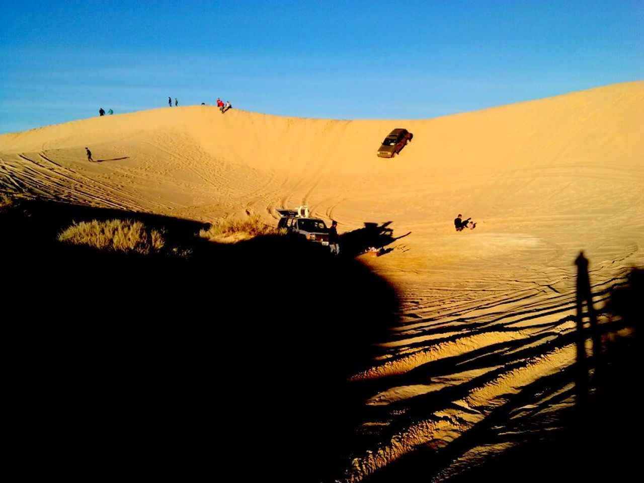 sand, sand dune, outdoors, desert, silhouette, landscape, clear sky, nature, sunlight, shadow, day, sky, people