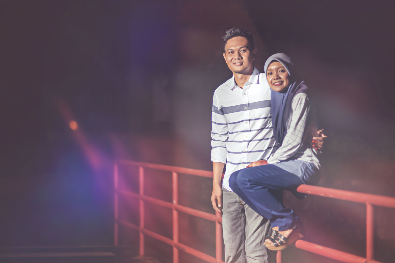 young men, smiling, young adult, two people, leisure activity, young women, real people, happiness, casual clothing, togetherness, looking at camera, lifestyles, portrait, couple - relationship, outdoors, night