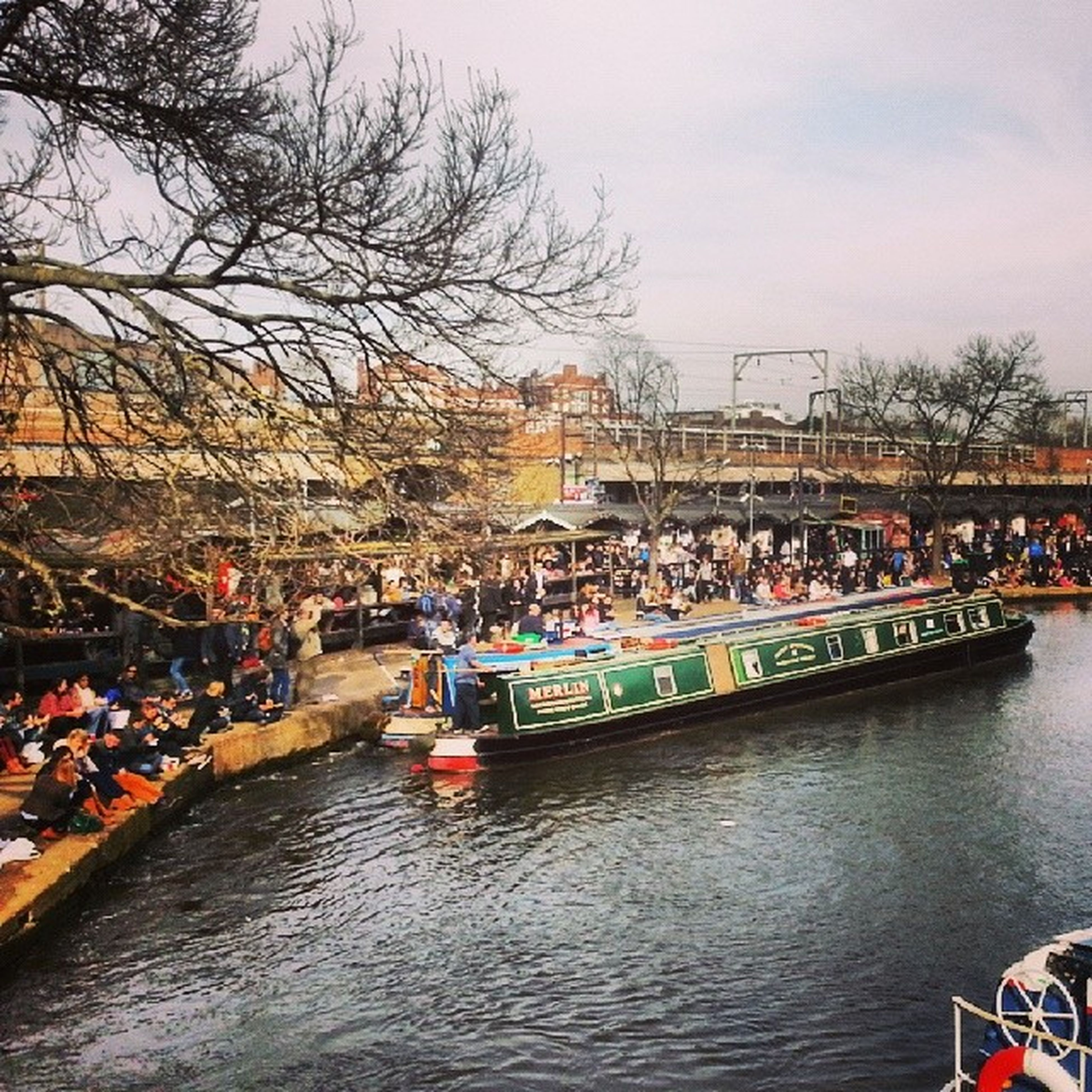 water, waterfront, architecture, built structure, building exterior, transportation, river, sky, nautical vessel, tree, mode of transport, large group of people, canal, city, rippled, boat, day, outdoors, incidental people