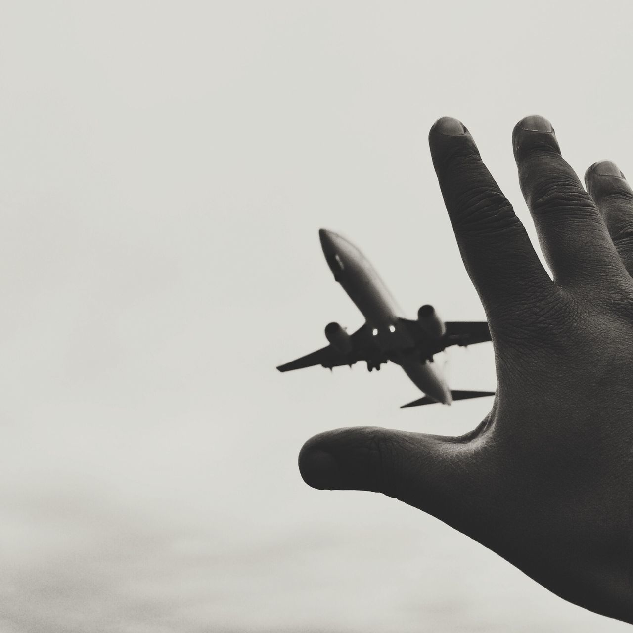 Optical Illusion Of Hand Reaching Airplane Against Sky