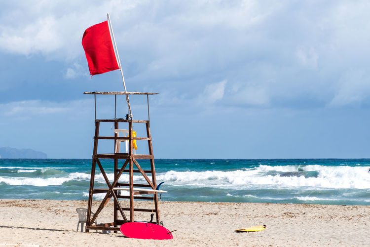 Krull&Krull Images Mallorca Beach Beauty In Nature Cloud - Sky Day Flag Horizon Over Water Life Guard Nature No People Outdoors Red Sand Scenics Sea Sky Son Serra De Marina Stormy Tranquil Scene Tranquility Water Wave An Eye For Travel