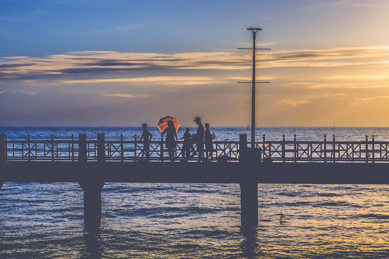 Silhouette People On Pier Over Sea At Sunset