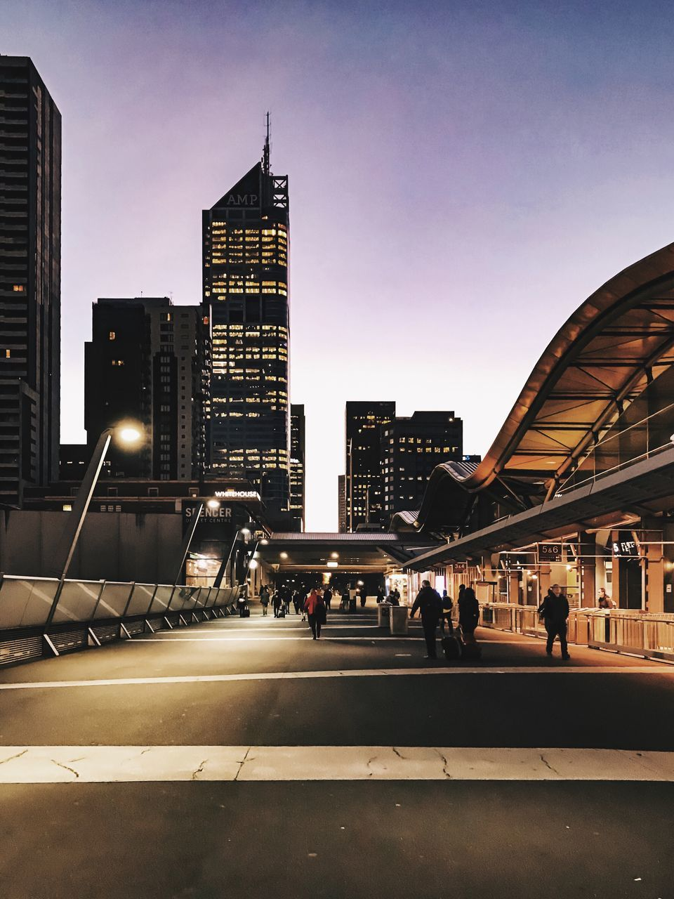 architecture, built structure, building exterior, city, skyscraper, modern, illuminated, city life, real people, travel destinations, large group of people, transportation, outdoors, men, sky, day, people