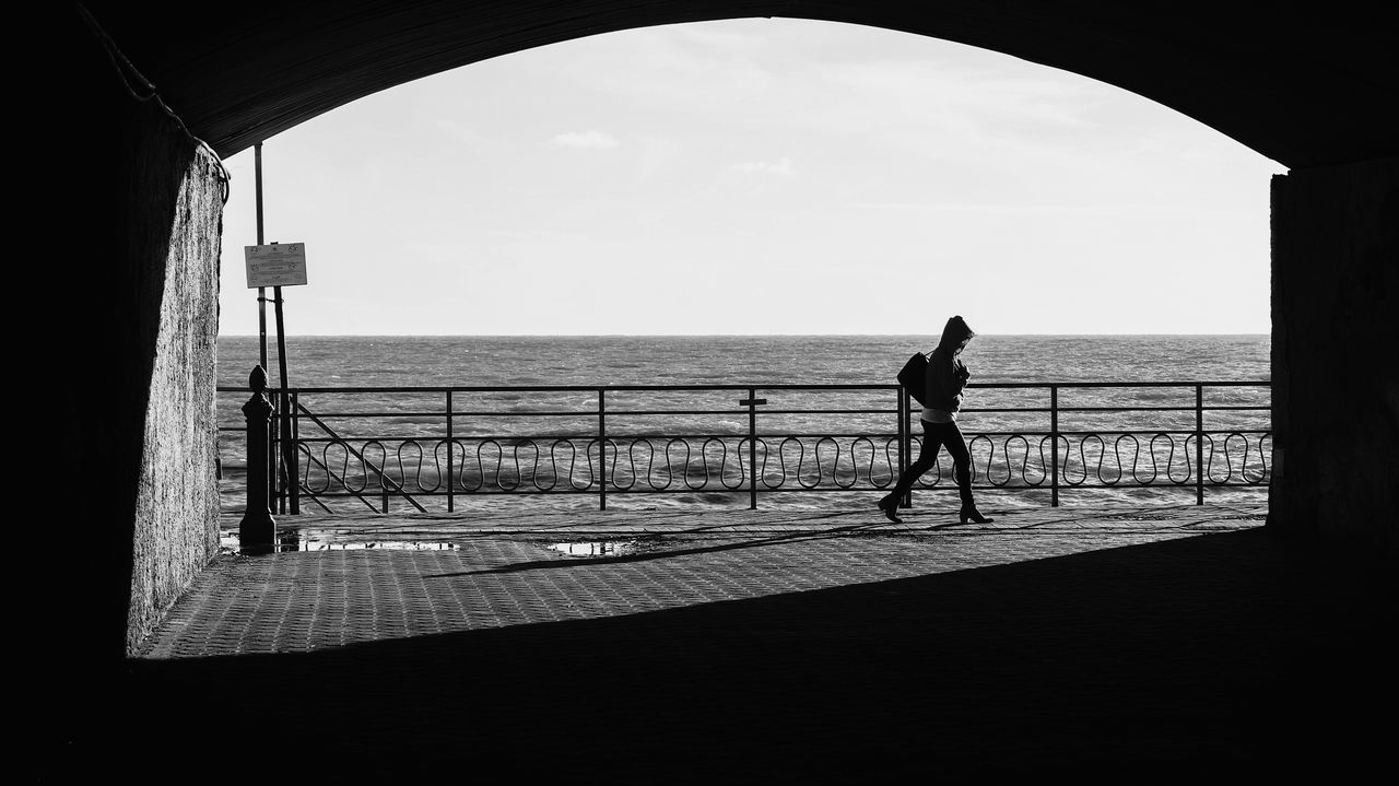 Windy Sea Full Length Horizon Over Water Standing Sky Beach Arch One Person Connection Adults Only People Day Outdoors Architecture Water Adult Only Men One Man Only Silhouette Streetphotography Eye4photography  EyeEm Best Shots Open Edit Fresh 3 Street Photography