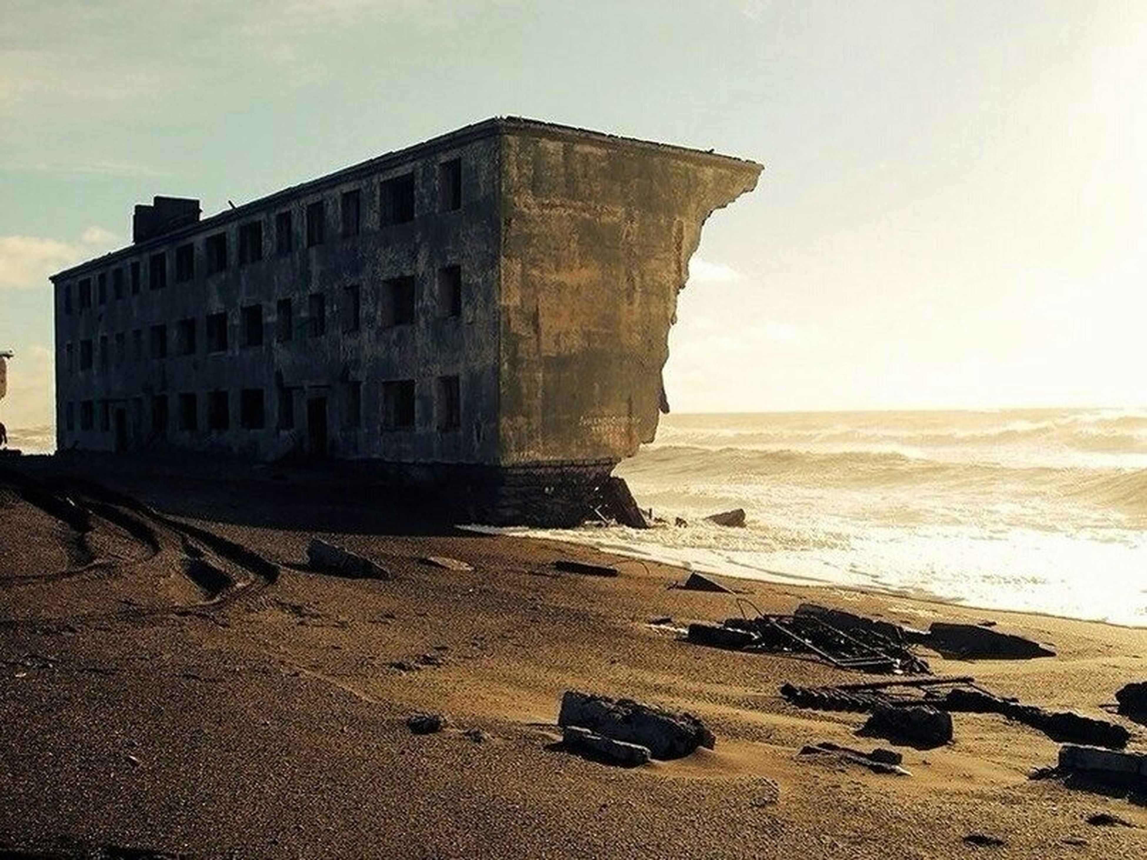 built structure, architecture, beach, sky, building exterior, sea, sand, water, shore, history, horizon over water, old, abandoned, travel destinations, old ruin, day, the past, outdoors, no people, sunlight