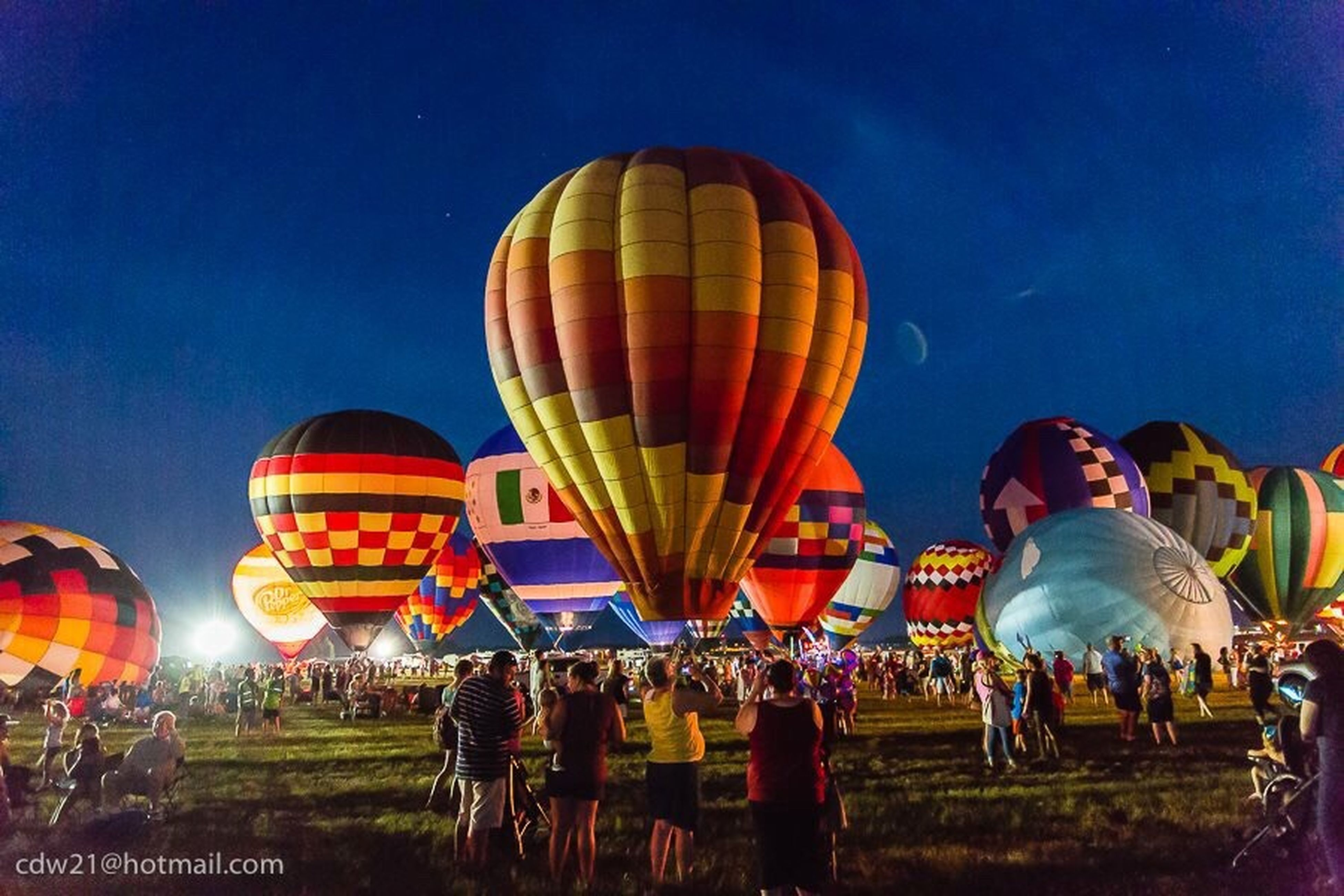 leisure activity, lifestyles, arts culture and entertainment, fun, enjoyment, blue, sky, amusement park ride, hot air balloon, illuminated, outdoors, multi colored, casual clothing, group of people, grass