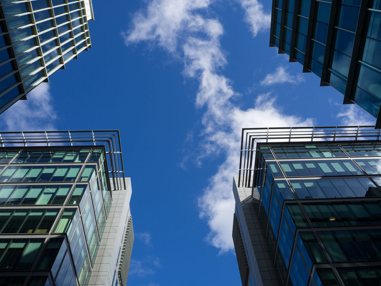 low angle view, sky, architecture, cloud - sky, built structure, building exterior, day, no people, outdoors, sunlight, blue, skyscraper, modern