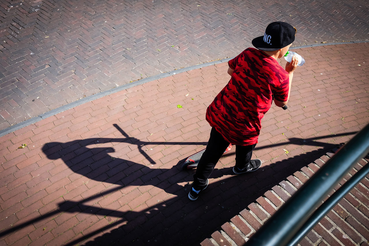 Haunted by shadow Amersfoort Cap Day Footpath High Angle View Holland Lifestyles Netherlands One Person Outdoors People Real People Rear View Red Shadow Sunlight