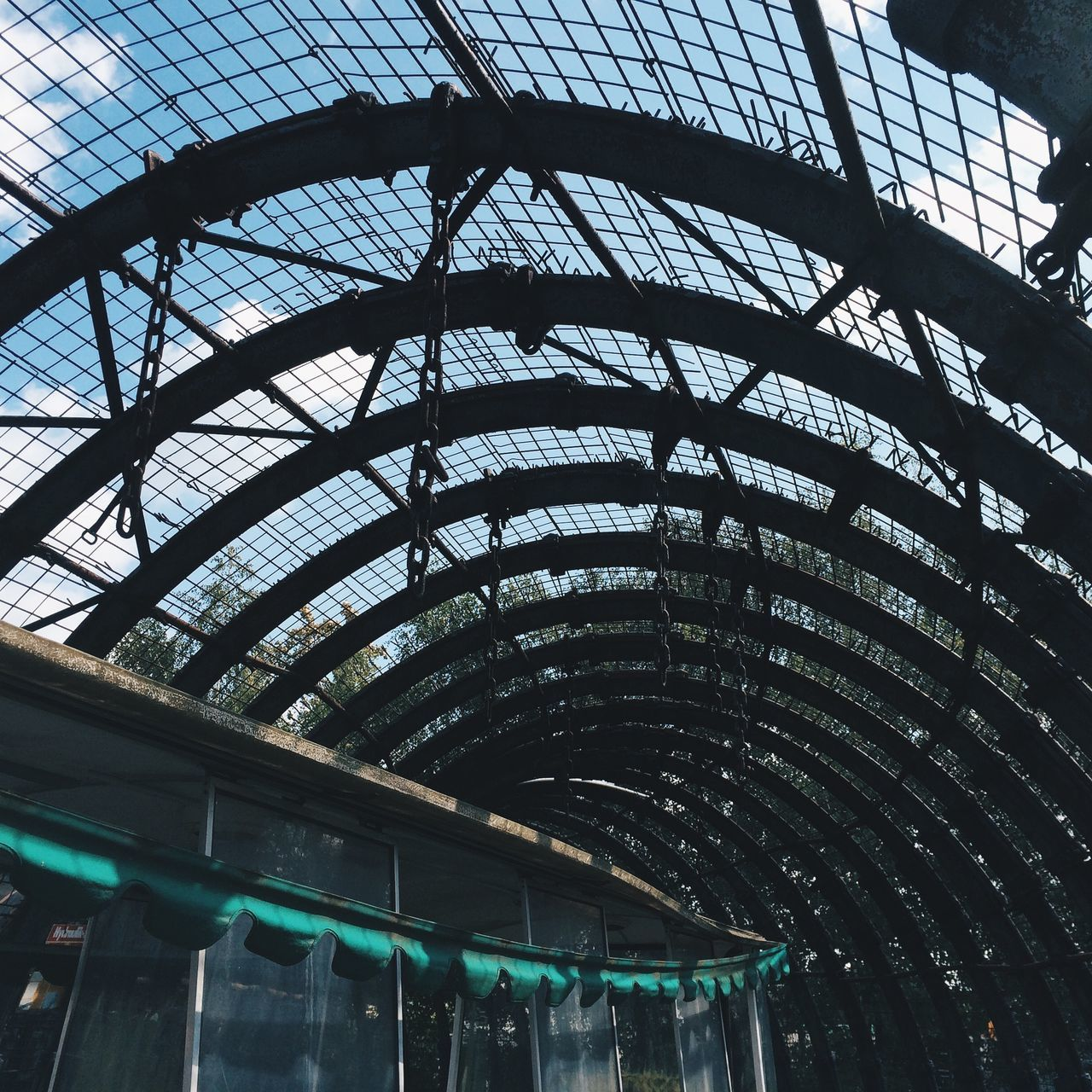 built structure, low angle view, indoors, ceiling, architecture, day, modern, travel destinations, no people, city, sky
