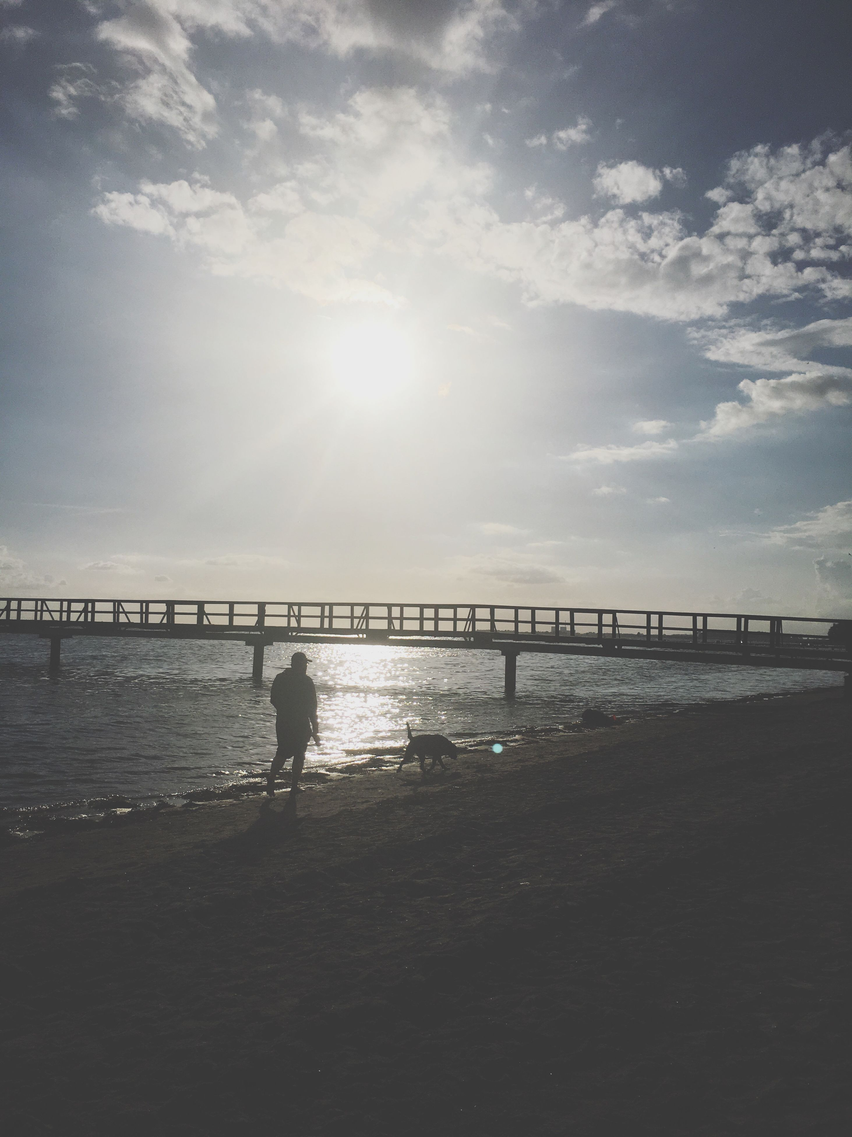 sea, beach, water, sunlight, sky, silhouette, railing, nature, outdoors, one person, sun, horizon over water, sunset, standing, sand, tranquil scene, scenics, leisure activity, tranquility, beauty in nature, day, full length, real people, people