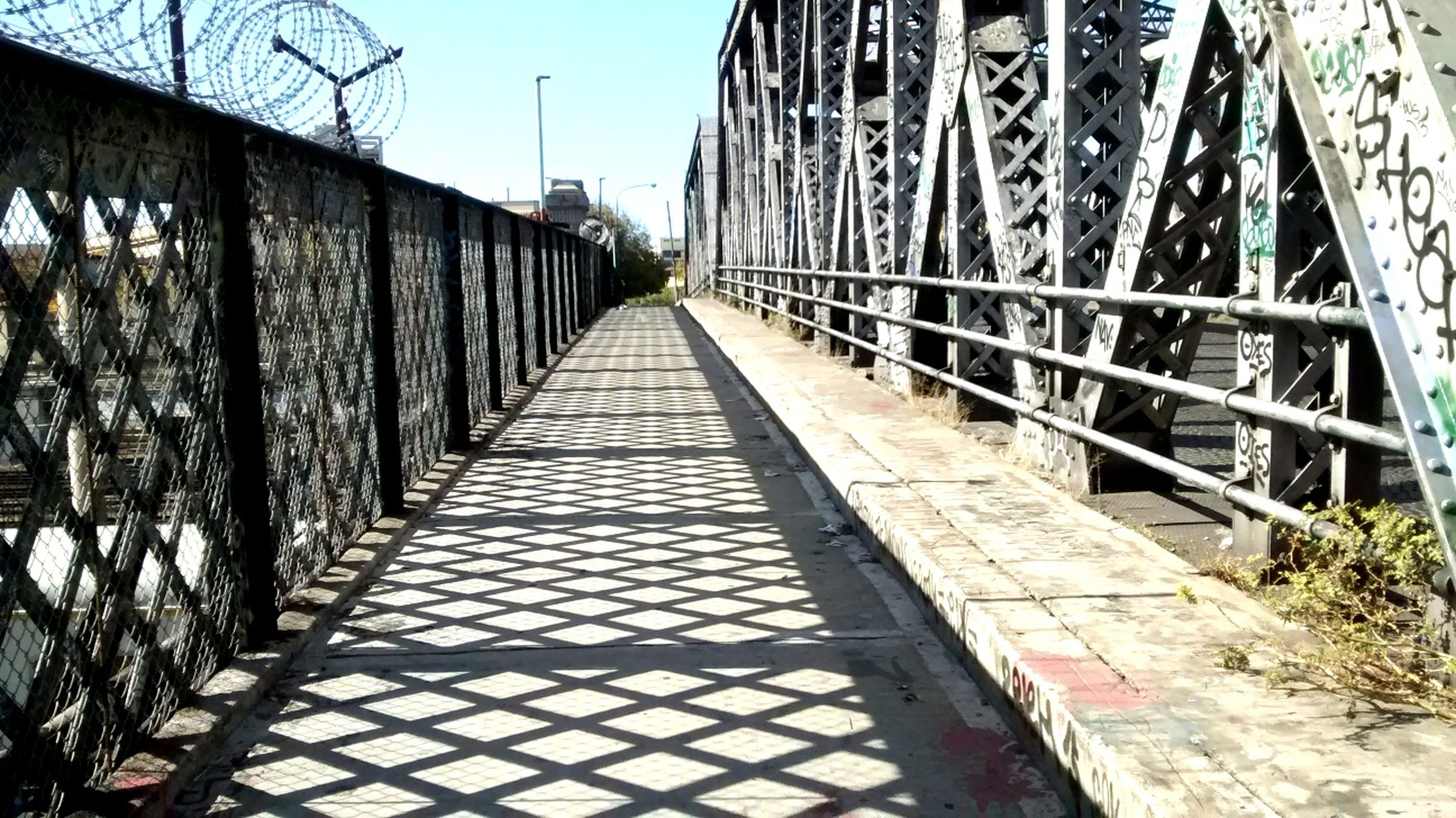 built structure, architecture, the way forward, diminishing perspective, connection, vanishing point, bridge - man made structure, railing, long, sky, footbridge, building exterior, tree, metal, day, sunlight, outdoors, narrow, clear sky, walkway