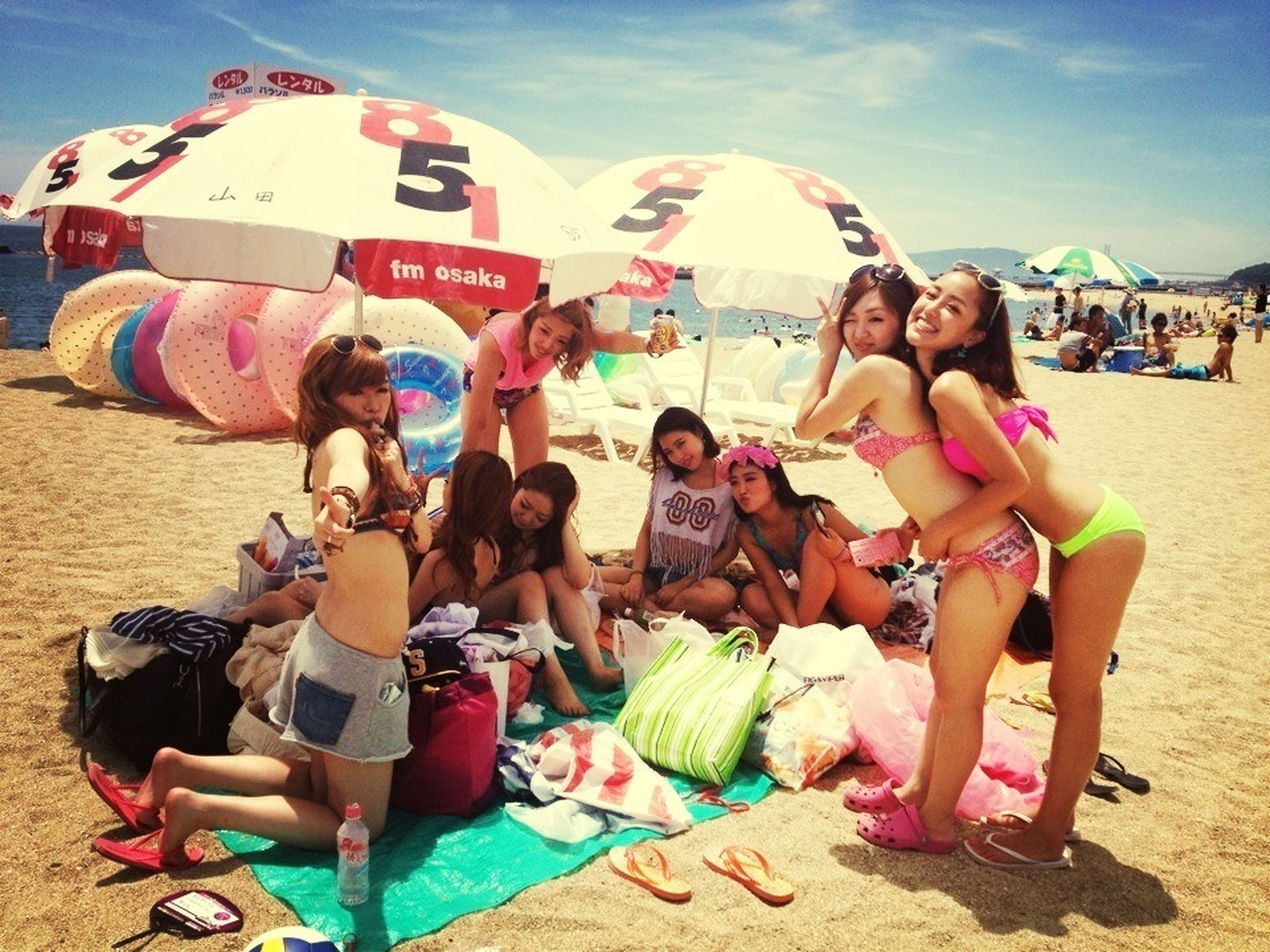 lifestyles, leisure activity, togetherness, casual clothing, fun, enjoyment, sitting, playing, full length, vacations, beach, sky, friendship, love, large group of people, bonding, person, childhood, happiness