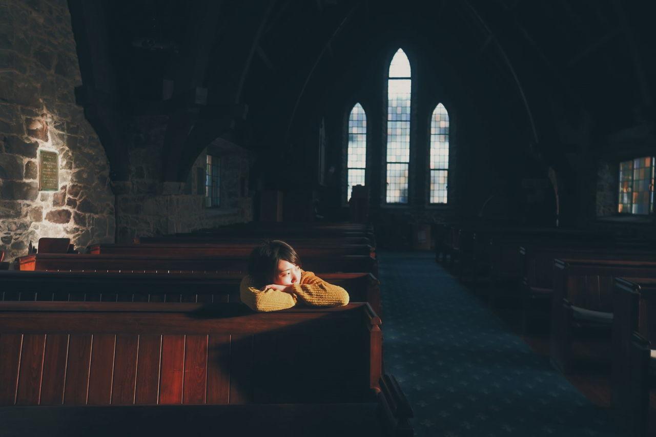 YOUNG WOMAN SITTING IN DARK CHRISTIAN CHURCH