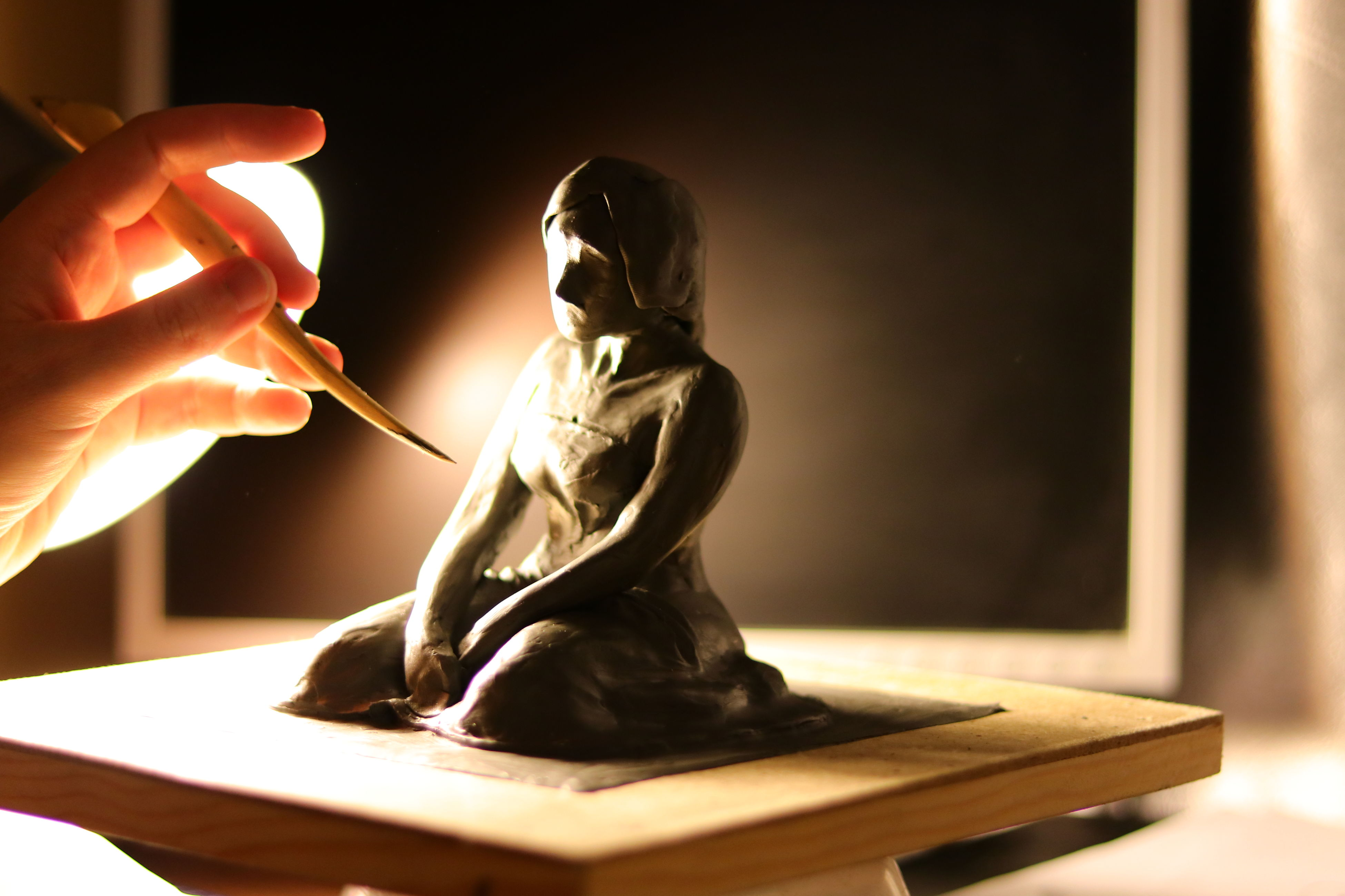 indoors, statue, real people, one person, sculpture, sitting, close-up, human hand, day