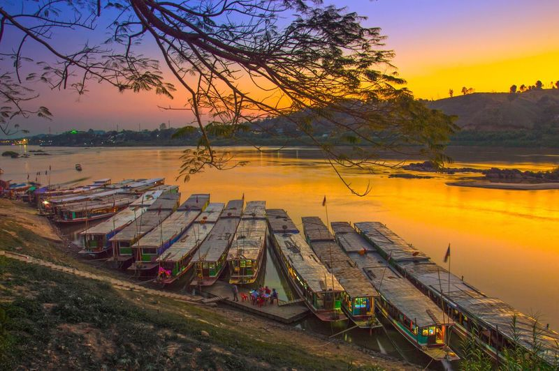 Boats docked at Houayxay port, Bokeo Province, Lao PDR., during sunset over Mekong River Sunset Water Houayxay Transportation Nature Mode Of Transport Scenics Nautical Vessel Sky Tranquil Scene Outdoors Tranquility Beauty In Nature No People Lake Moored Bare Tree Day Laos Bokeo River Port Pier Boat Luangprabang The Great Outdoors - 2017 EyeEm Awards