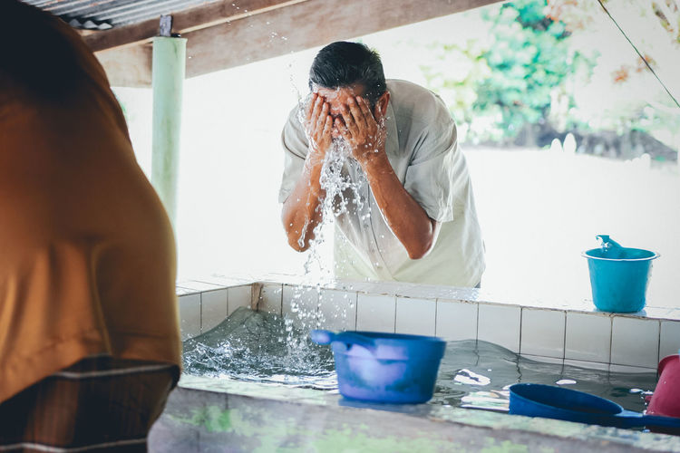 Body Care Day Domestic Life Freshness Holding Hygiene Indoors  Leisure Activity Lifestyles Mid Adult Mid Adult Men Muslim One Person People Preparation  Real People Standing Water Wudoe Wudu