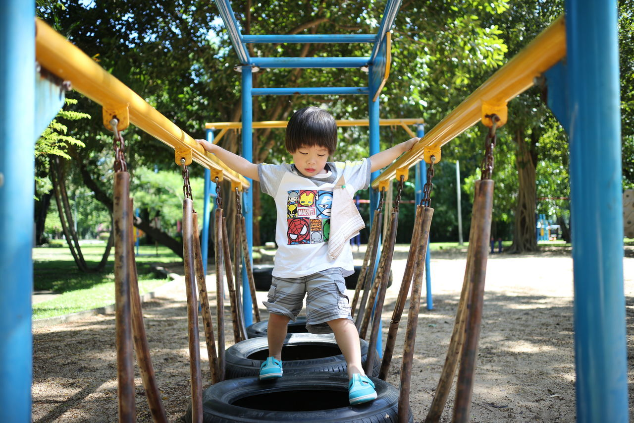 kid in park Baseball Bat Child Childhood Children Only Day Full Length Fun Garden Happiness Human Body Part Jungle Gym Nature One Boy Only One Person Outdoor Play Equipment Outdoors Park Park - Man Made Space People Playground Playing Swing Tree