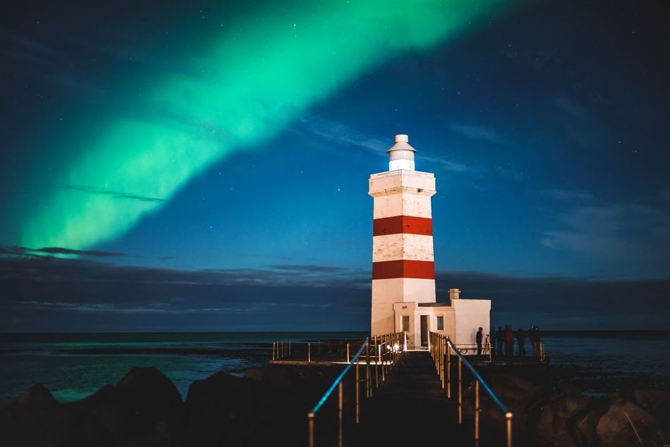 At the far end of the country, the lights let us know we made it. Night Travel Lighthouse Nature Sea Sky Illuminated Outdoors Astronomy Full Frame Iceland Showcase: April Travel Destinations Travel Photography Natural Phenomenon Aurora Borealis Northern Lights Europe