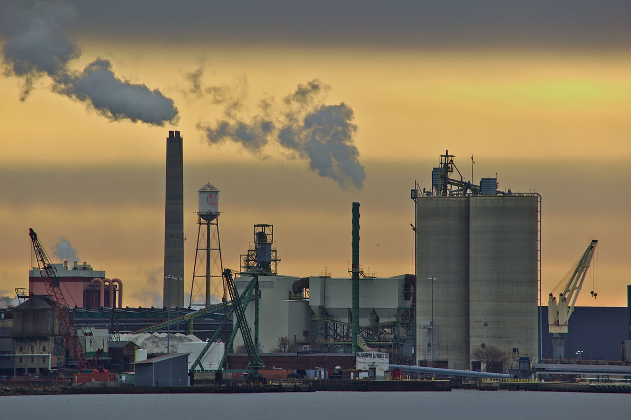 Industrial riverfront landscape with pollution and water. Air Pollution Environment Factory Fuel And Power Generation Gas Industry Night No People Outdoors Sky Smoke - Physical Structure Smoke Stack Social Issues Sunset Urban Skyline