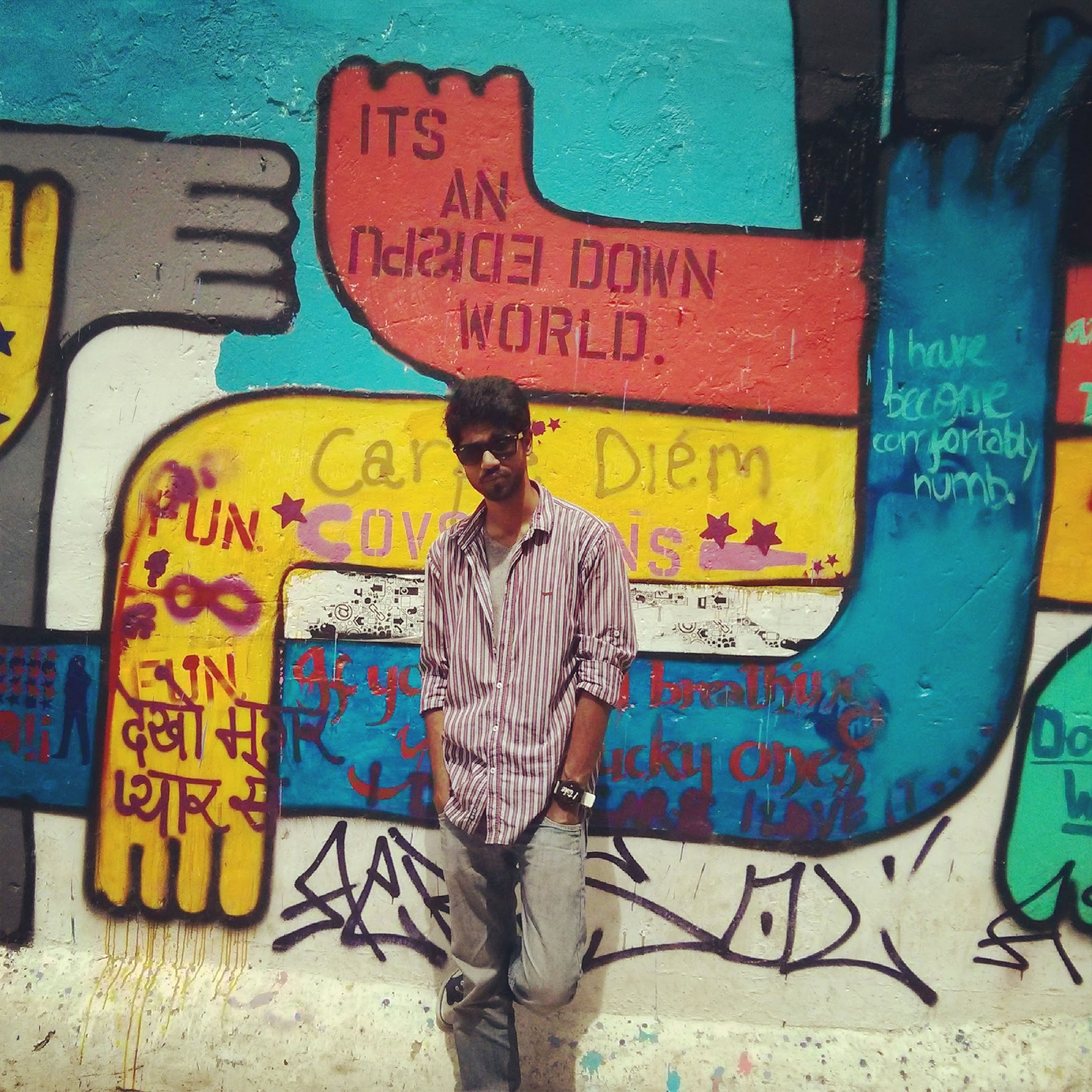 text, lifestyles, communication, western script, graffiti, casual clothing, standing, leisure activity, wall - building feature, full length, blue, three quarter length, day, front view, young adult, outdoors, person, art