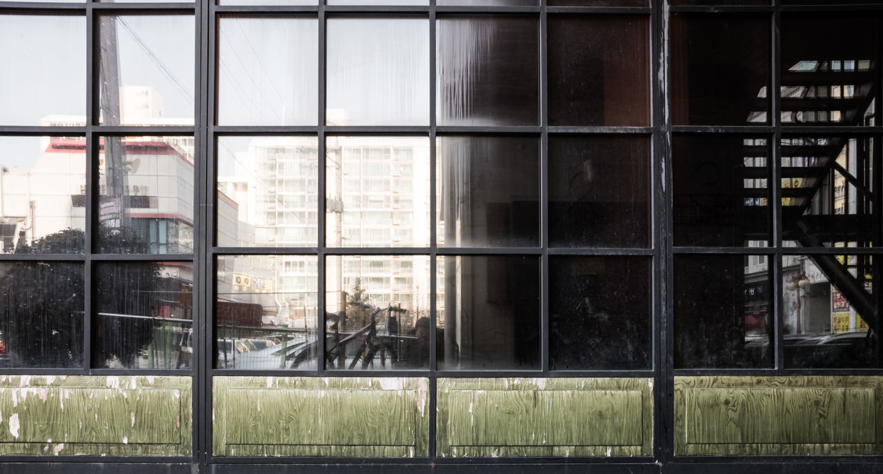 Cityscape reflected in windows and doors of a shopping mall Doors Architecture Building Exterior Built Structure Cityscape Day No People Outdoors Shopping Mall Sliding Door Window