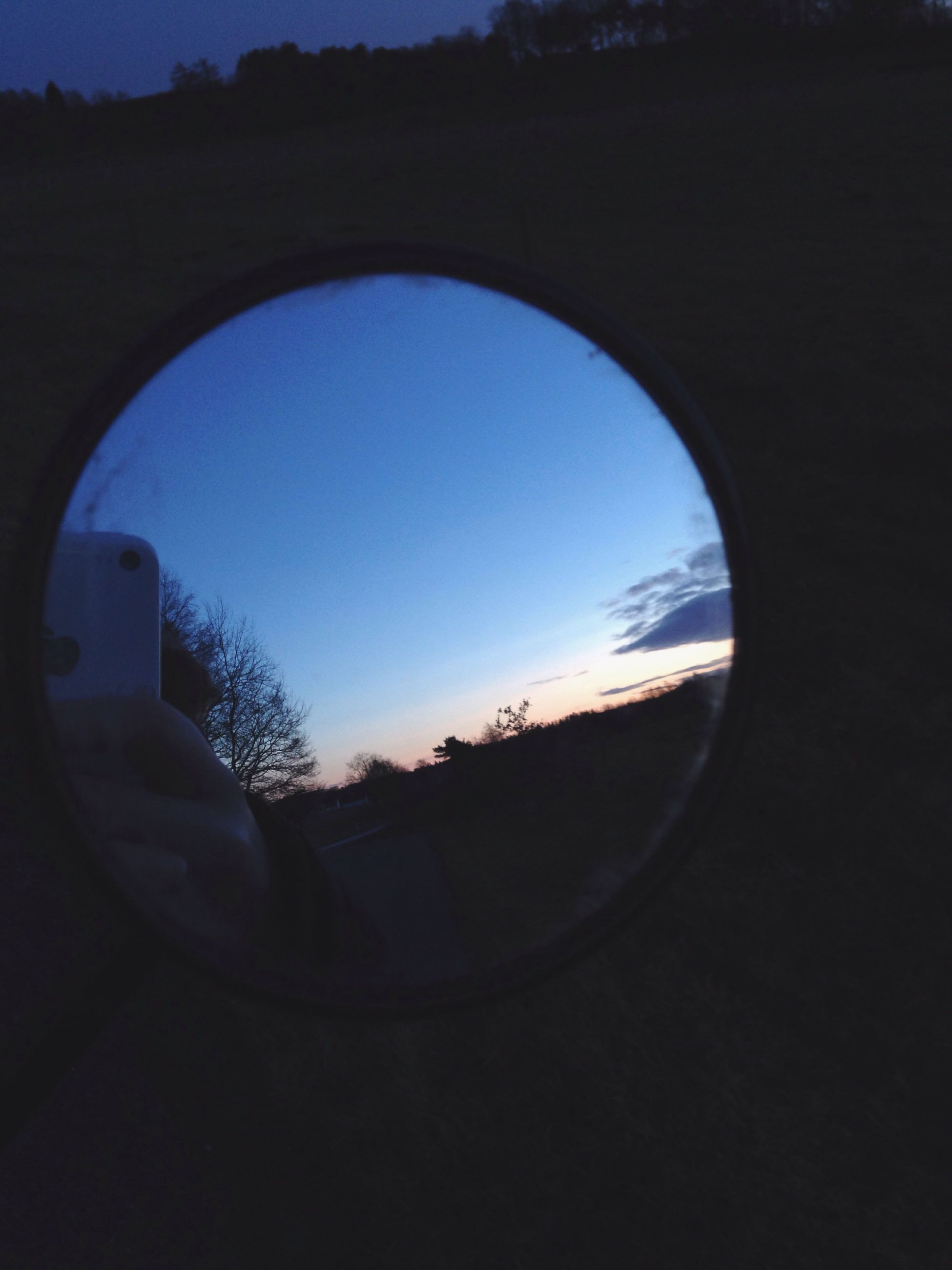 circle, sky, geometric shape, tree, silhouette, reflection, window, indoors, fish-eye lens, cloud - sky, arch, nature, blue, built structure, round, no people, transparent, cloud, landscape, tranquility