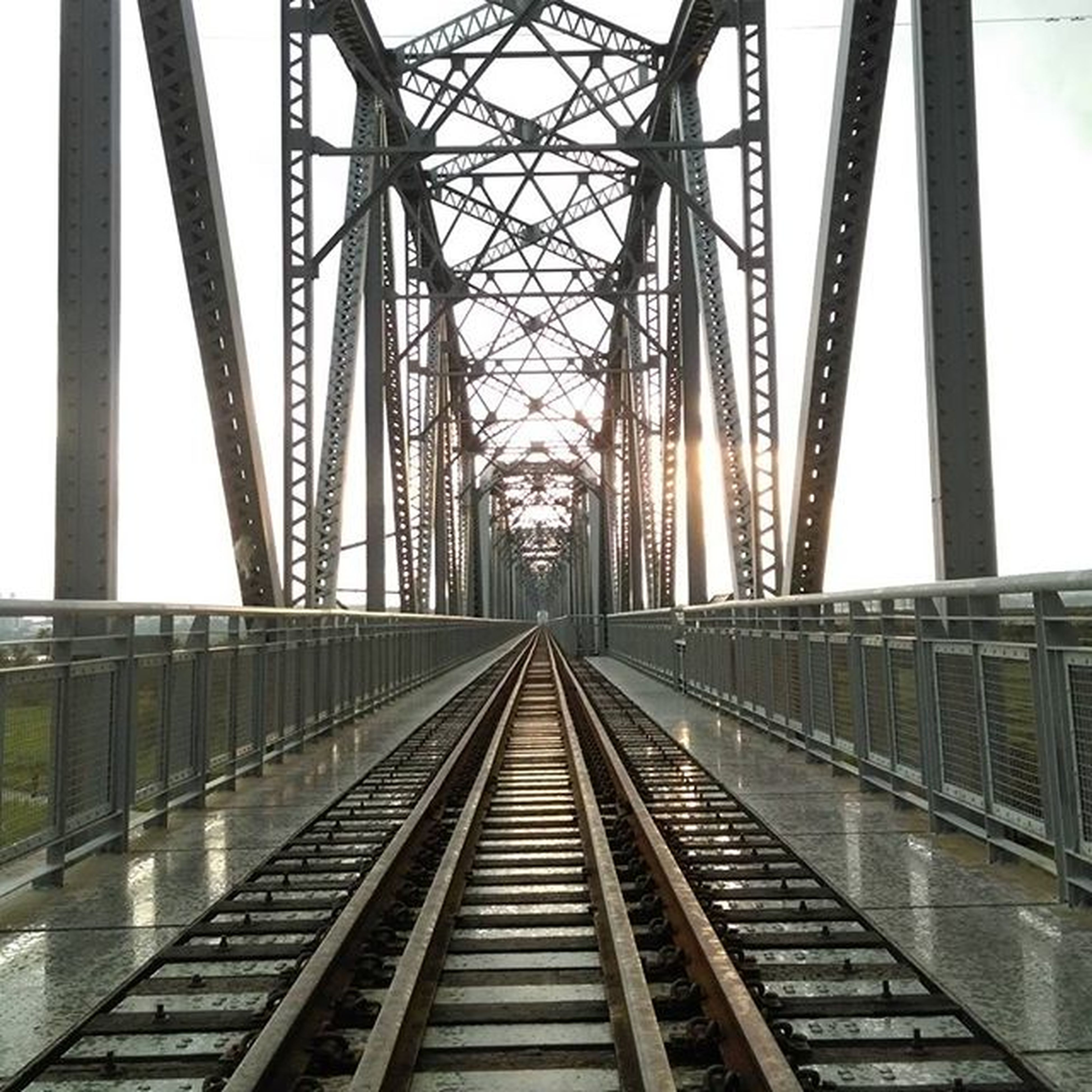 architecture, built structure, connection, diminishing perspective, bridge - man made structure, transportation, the way forward, metal, engineering, vanishing point, railroad track, rail transportation, metallic, low angle view, railway bridge, clear sky, sky, day, no people, long