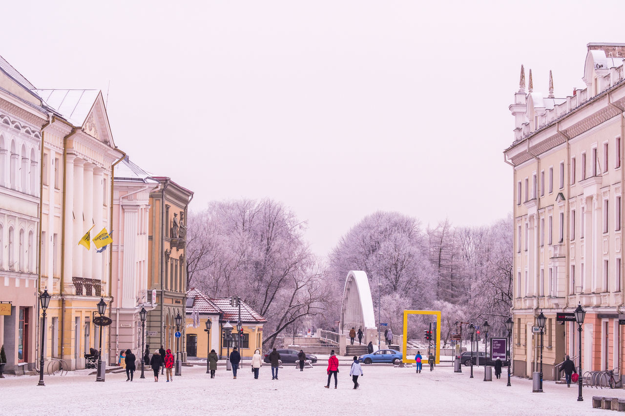 clear sky, built structure, building exterior, architecture, copy space, outdoors, day, tree, real people, winter, large group of people, sky, cold temperature, city, people